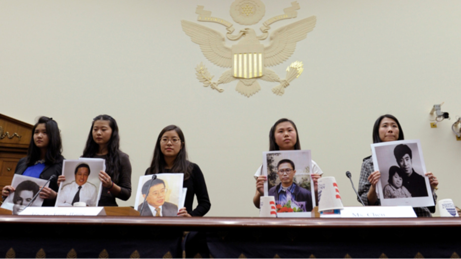 """Dec. 5, 2013: From left, Lisa Peng, holding a photo of her father Peng Ming, Grace Ge Geng, holding photo of her father Gao Zhisheng, Ti-Anna Wang, holding photo of her father Wang Bingzhang, Bridgette Chen holding photo of her father Liu Xianbing, and Danielle Wang, holding photo of her father Wang Zhiwen, are introduced prior to testifying before the House Foreign Affairs Committee hearing entitled, """"Their Daughters Appeal to Beijing: 'Let Our Fathers Go,! on Capitol Hill in Washington."""