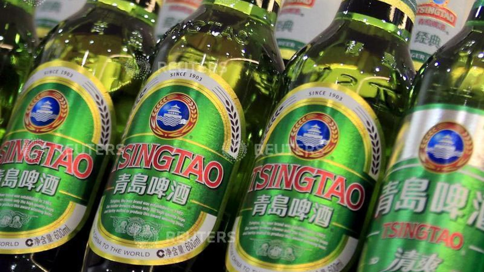 Bottles of Tsingtao beer are placed on shelves at a supermarket in Shanghai March 28, 2016. (REUTERS/Aly Song)