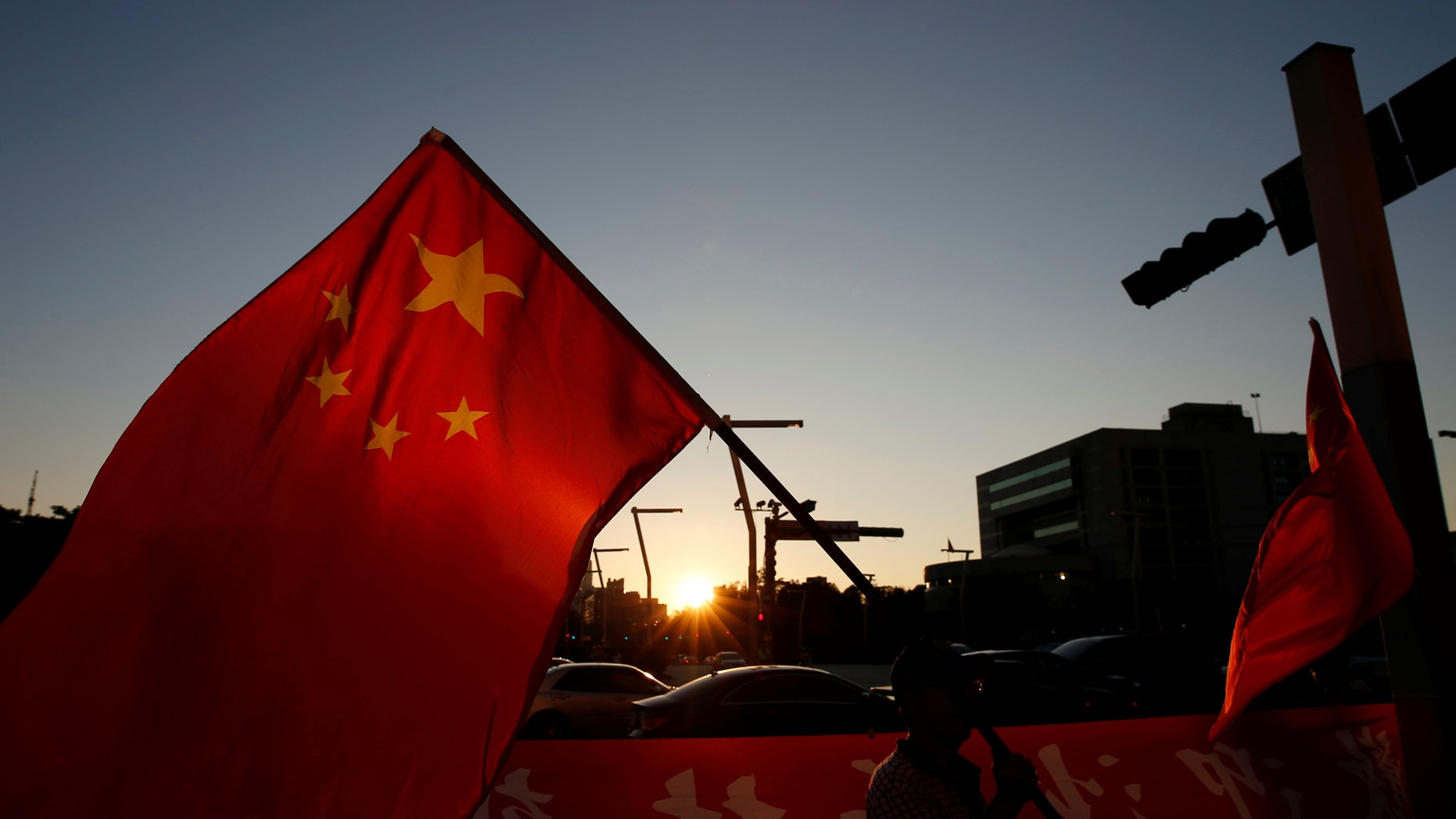 A pro-China supporter holds Chinese national flag, outside the dinner venue of Sha Hailin, a member of Shanghai's Communist Party standing committee, in Taipei, Taiwan August 22, 2016. (REUTERS/Tyrone Siu)