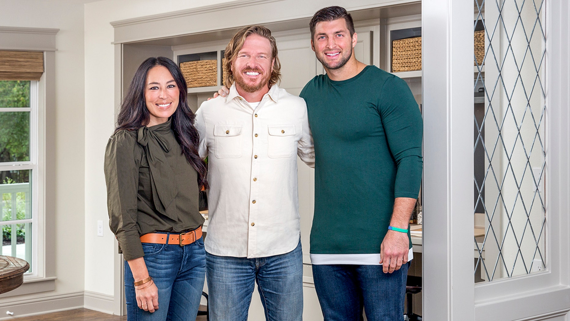 """""""Fixer Upper"""" stars Chip and Joanna Gaines pose with Tim Tebow, right."""