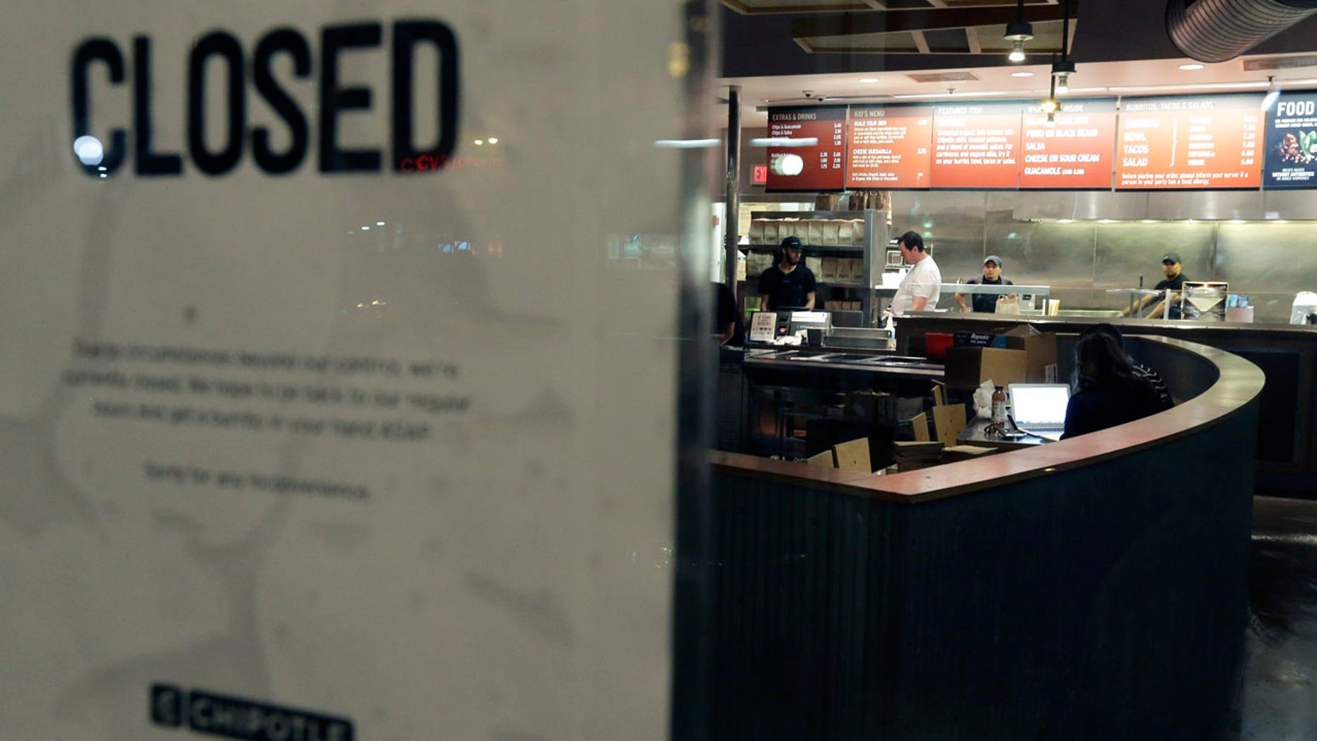 """Dec. 7, 2015: People stand inside a closed Chipotle restaurant in the Cleveland Circle neighborhood of Boston. Chipotle said late Monday that it closed the restaurant after several students at Boston College, including members of the men''s basketball team, reported """"gastrointestinal symptoms"""" after eating at the chain."""
