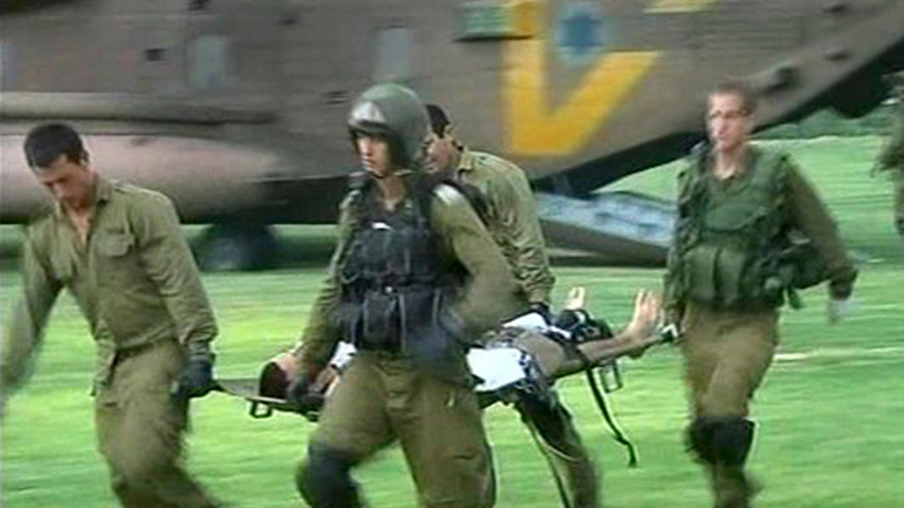 In this image provided by Associated Press Television News, an injured man is carried on a stretcher by helicopter crew on arrival at Soroka hospital in Beersheba, Israel, Aug. 18.