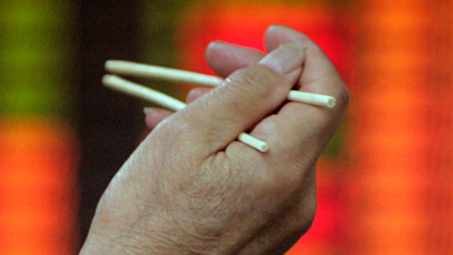 An investor holding a pair of chopsticks has his lunch in front of an electronic board at the stock exchange in Shanghai June 4, 2007. China's main stock index tumbled more than 7 percent on Monday, adding to big losses suffered last week after the government hiked the share trading tax to cool speculation. REUTERS/Aly Song (CHINA)Also see RTR1RHDZ