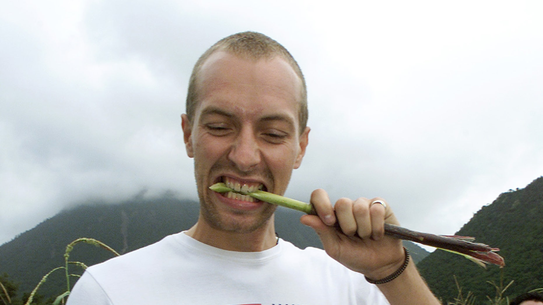 September 6, 2003. Coldplay band vocalist Chris Martin tastes a stalk of sweet corn canein a corn field owned by a cooperative in Puebla state, outside of Mexico City.