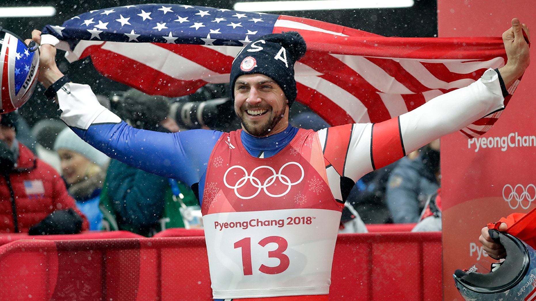 American Chris Mazdzer celebrates his historic silver medal win by eating a slice of pizza in one bite.