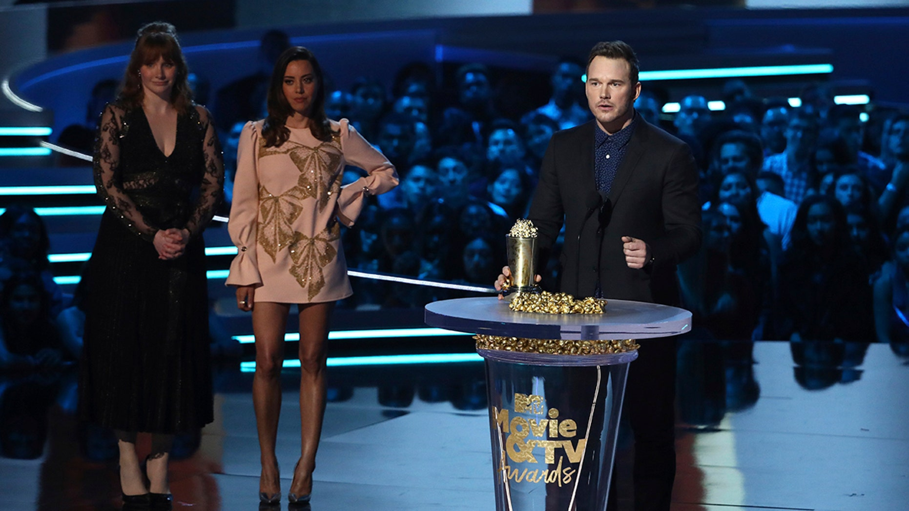 Chris Pratt accepts the generation award as Bryce Dallas Howard, from left, and Aubrey Plaza look on at the MTV Movie and TV Awards at the Barker Hangar in Santa Monica, Calif.