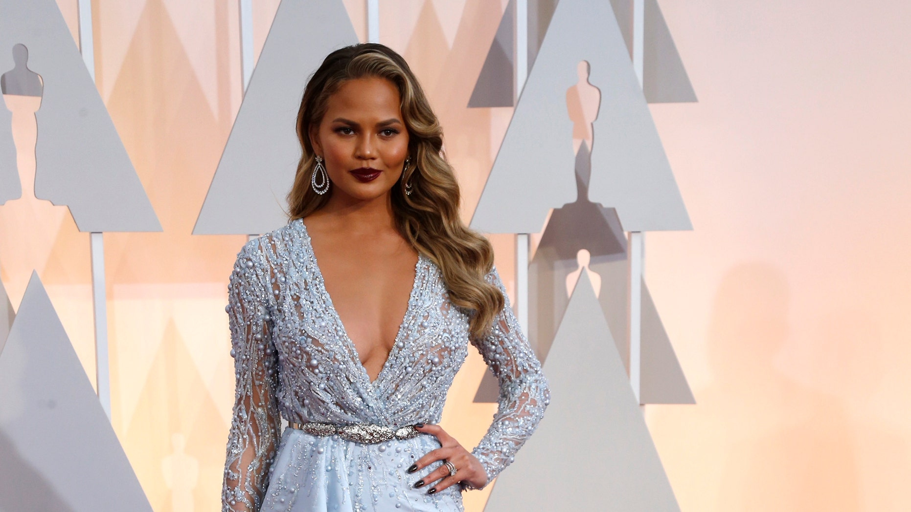 February 22, 2015. Model Chrissy Teigen, wearing a light blue bejeweled Zuhair Murad gown, arrives at the 87th Academy Awards in Hollywood, California.