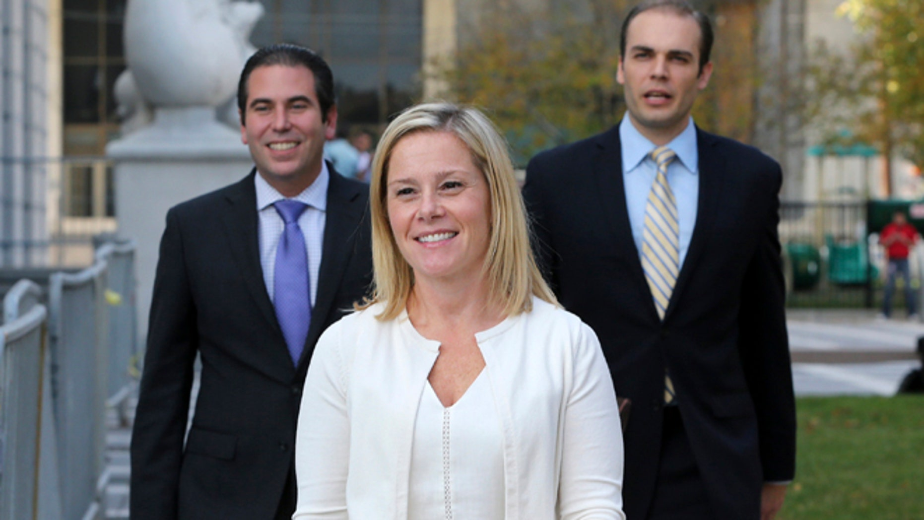 """FILE - In this Wednesday, Oct. 19, 2016 file photo, Gov. Chris Christie's former Deputy Chief of Staff Bridget Anne Kelly, center, leaves Martin Luther King Jr. Courthouse after a hearing, in Newark, N.J. Kelly, who prosecutors say sent the """"time for some traffic problems"""" email that started the George Washington Bridge lane-closing scandal is set to testify in her own defense. Kelly is expected to take the stand later Friday, Oct. 21, 2016, in federal court in Newark. (AP Photo/Mel Evans, File)"""