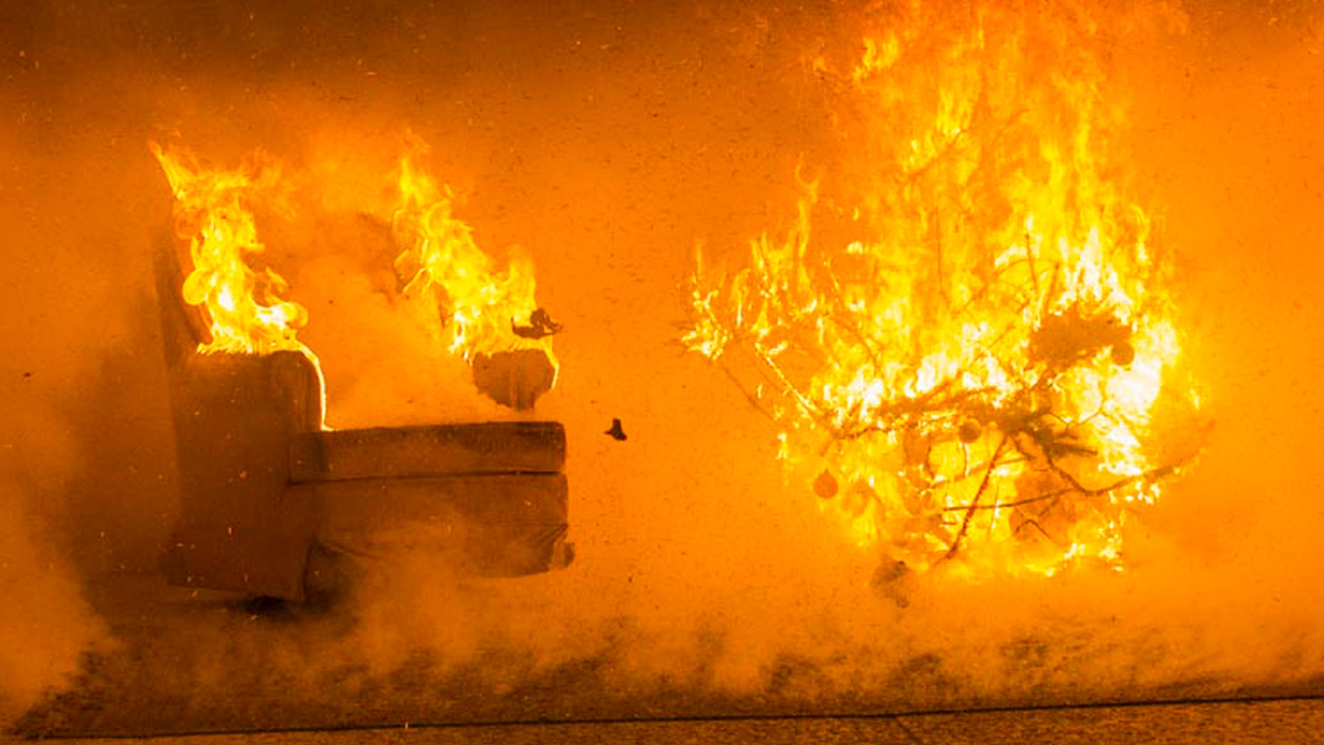 In this Tuesday, Nov. 29, 2016 photo flames engulf the wall and ceiling of a room as well as items in the room thirty-five seconds into the ignition of a Christmas tree during a test burn by the fire protection engineering lab at the Worcester Polytechnic Institute, in Worcester, Mass.