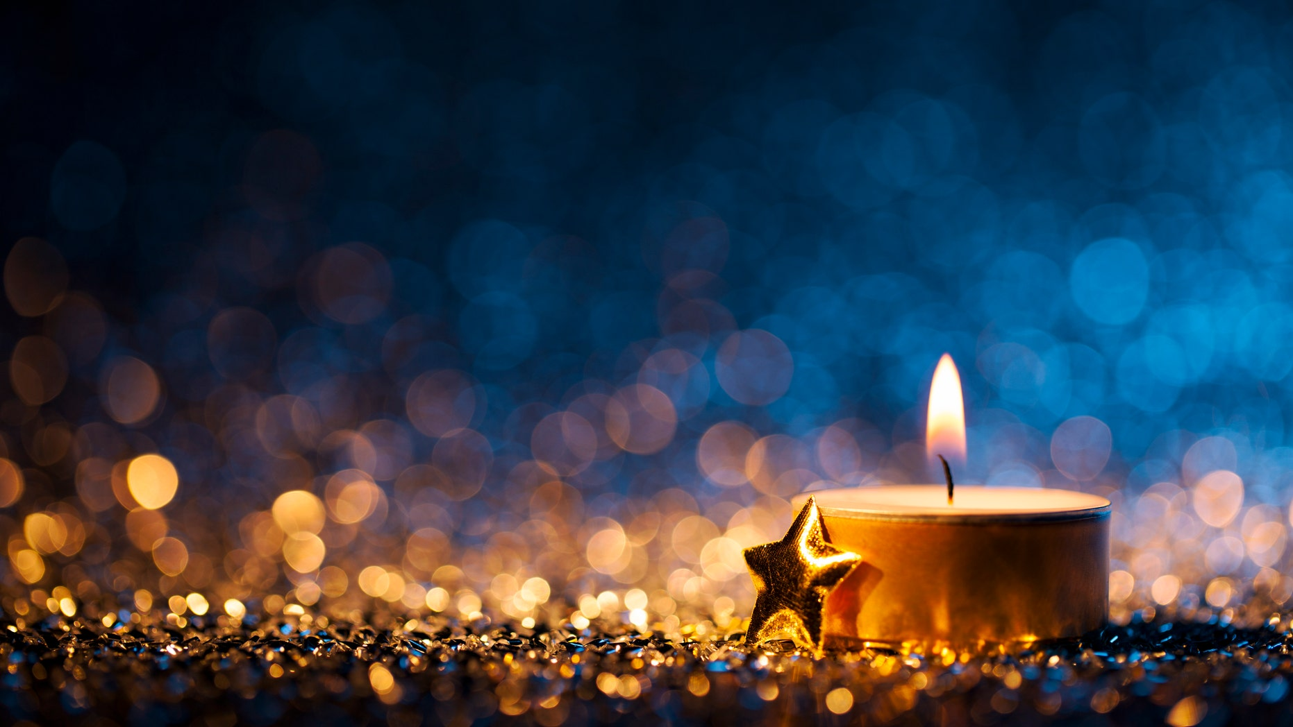 Tea light and a golden star on defocused blue and gold background.
