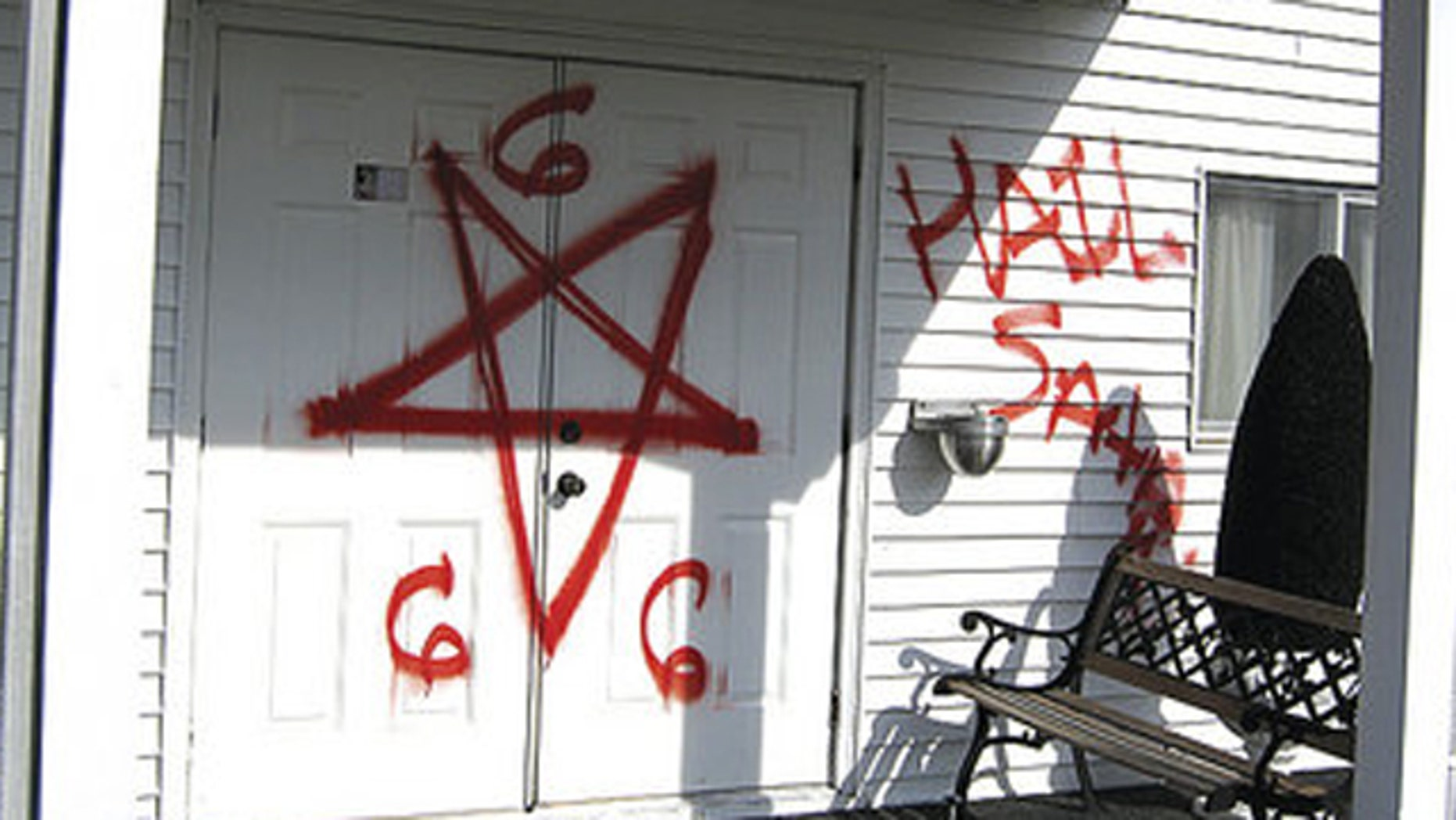 """Bright red spray-paint was used to write """"Hail Satan"""" and """"666""""outside walls of Gospel Light Missionary Baptist Church."""