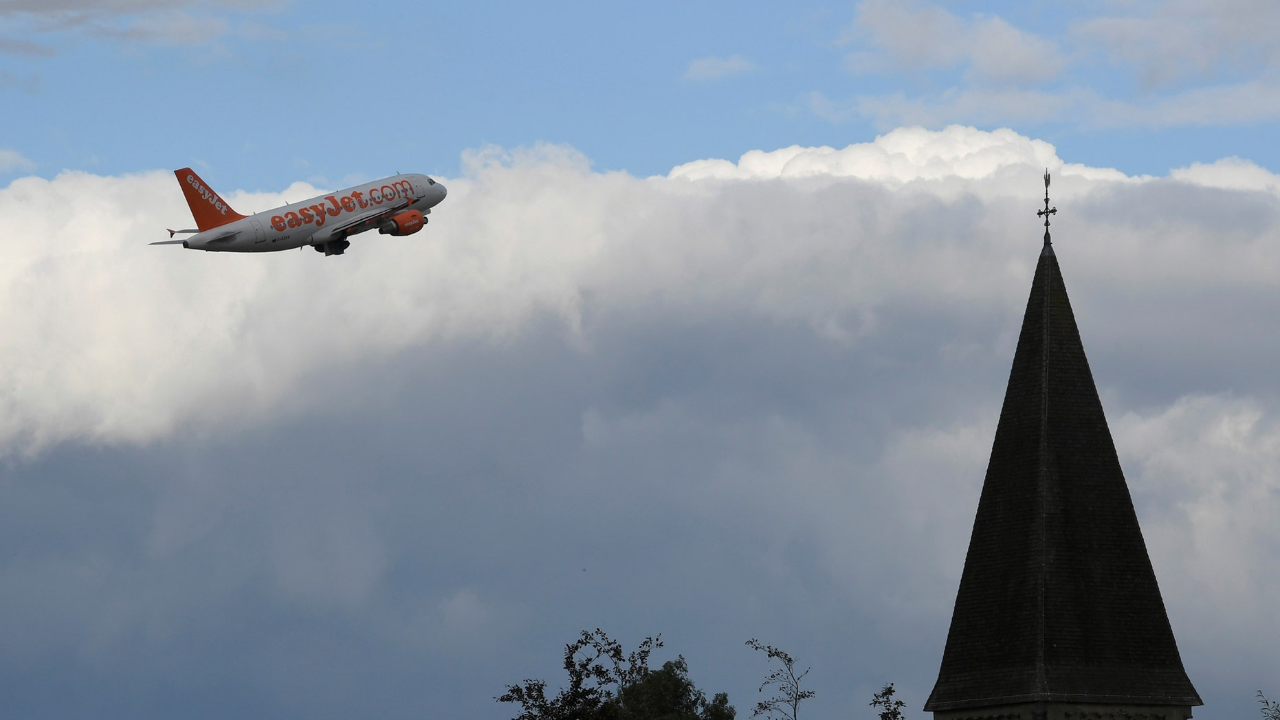 File photo - An EasyJet passenger aircraft is seen behind a church steeple as it takes off from Gatwick Airport in southern England, Britain, Oct. 9, 2016. (REUTERS/Toby Melville)