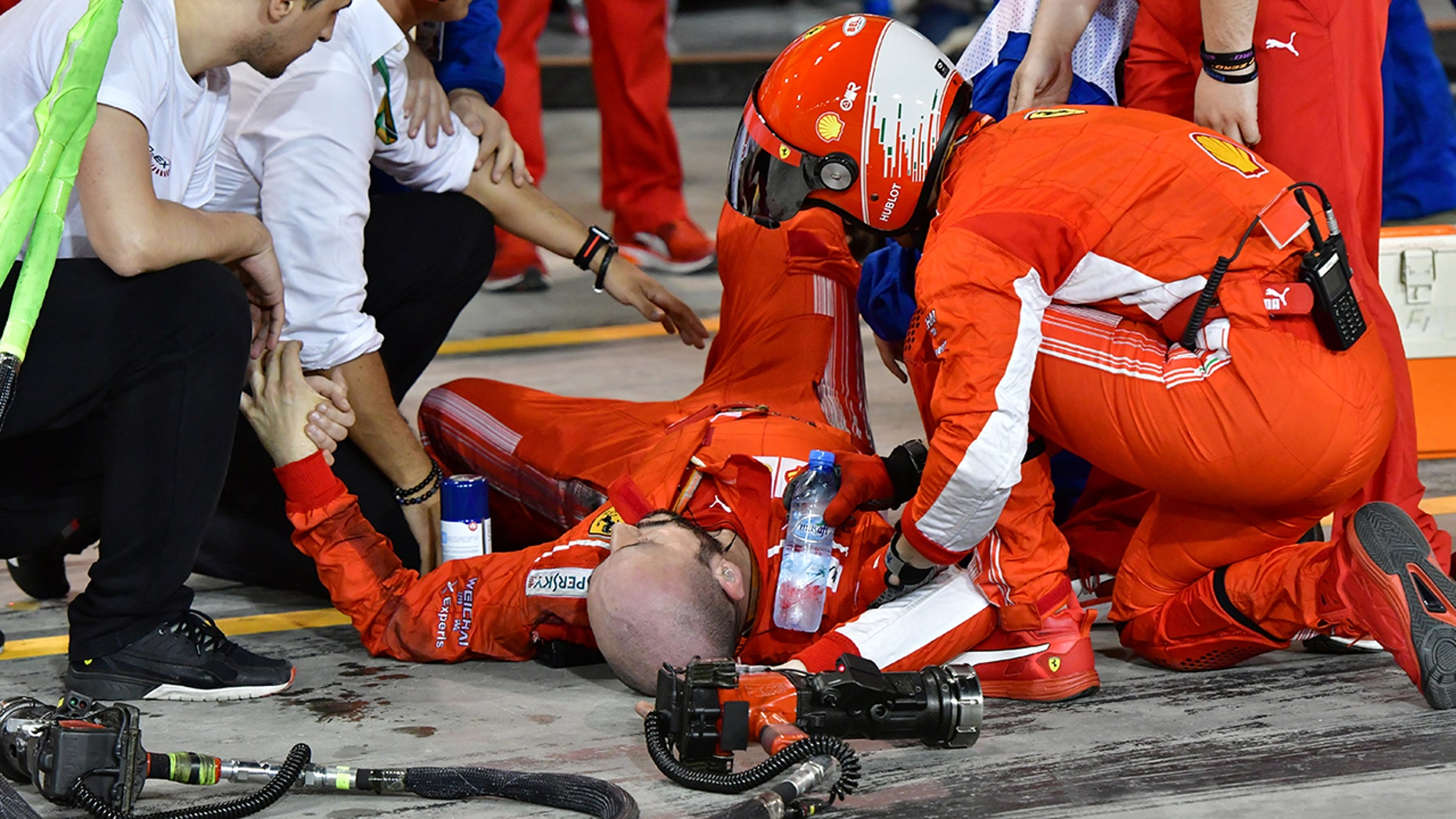 Teammates aid Francesco Cigarini after he was hit by Kimi Raikonnen's F1 car.