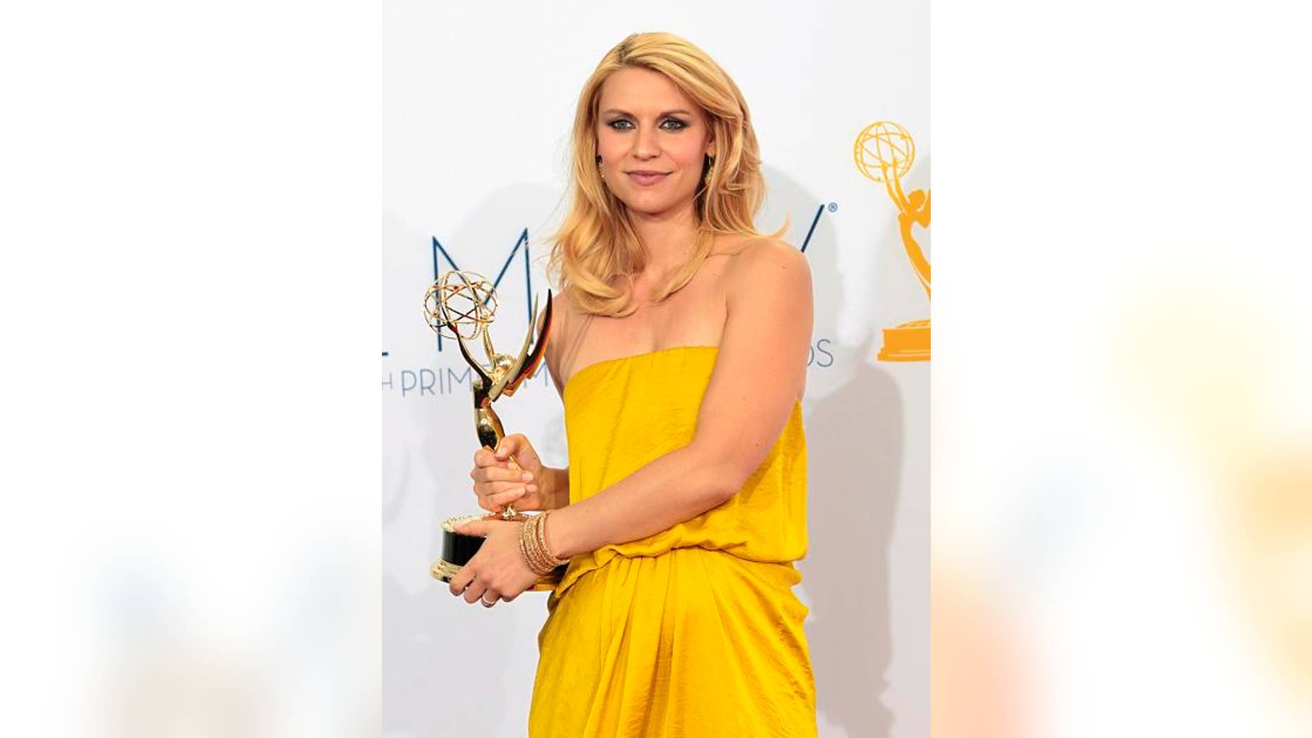 """Claire Danes holds the Emmy award for outstanding lead actress in a drama series for her role in """"Homeland"""" at the 64th Primetime Emmy Awards in Los Angeles September 23, 2012.  REUTERS/Mario Anzuoni (UNITED STATES  Tags: ENTERTAINMENT) (EMMYS-BACKSTAGE)"""