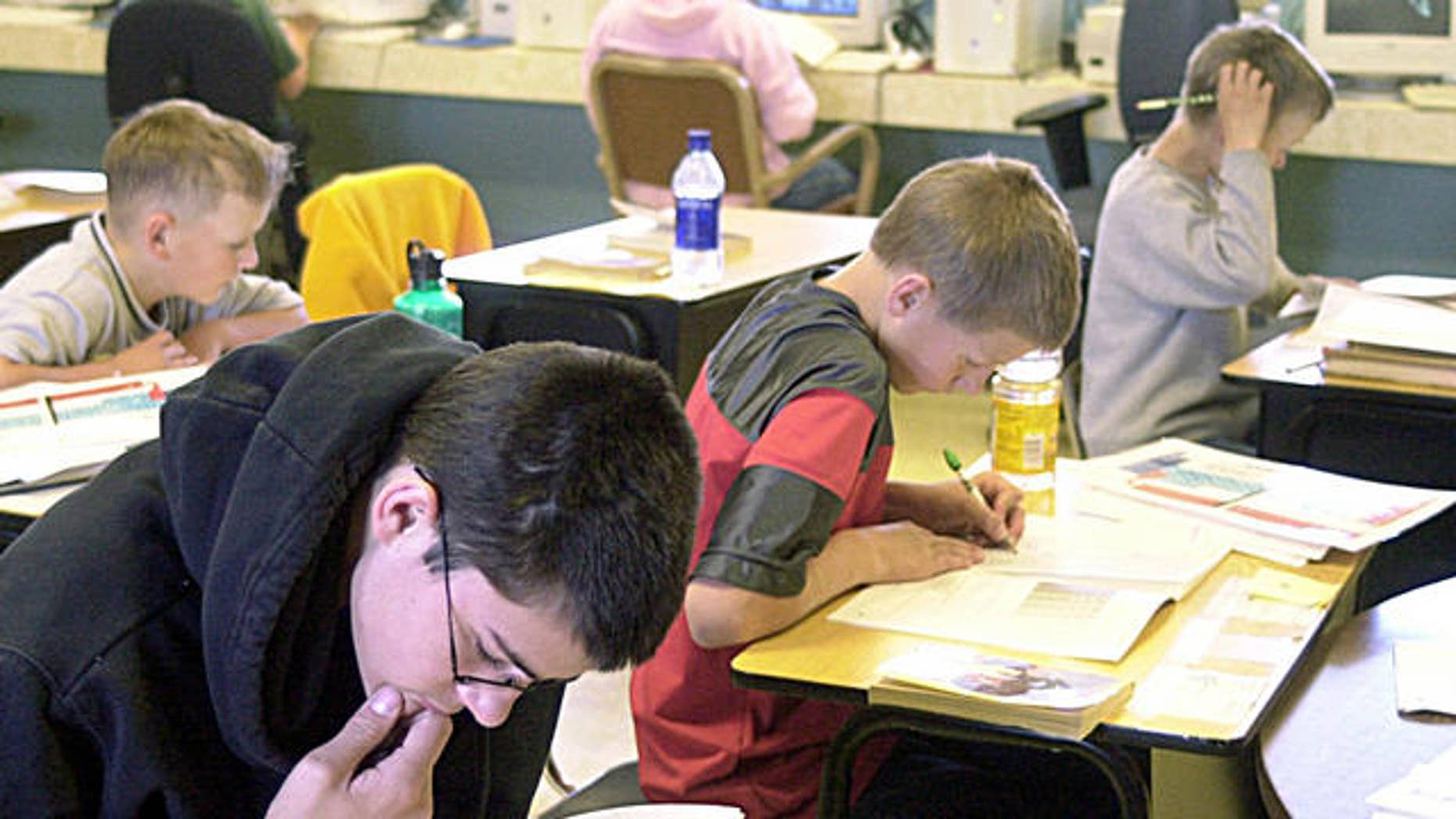 ** FILE **Eighth-grader Ethan Woosley, left, reads while fifth-graders, Ross Frank, middle, Tel Abbe, right, and Jeremiah Taylor, second row, study at Adel Middle School in the small south-central Oregon community of Adel, Ore., April 15, 2004. The U.S. Department of Education's recent announcement that teachers in rural schools would get more time to meet strict federal qualifications was greeted with an audible sigh of relief in schools from Colorado to California. (AP Photo/Don Ryan)