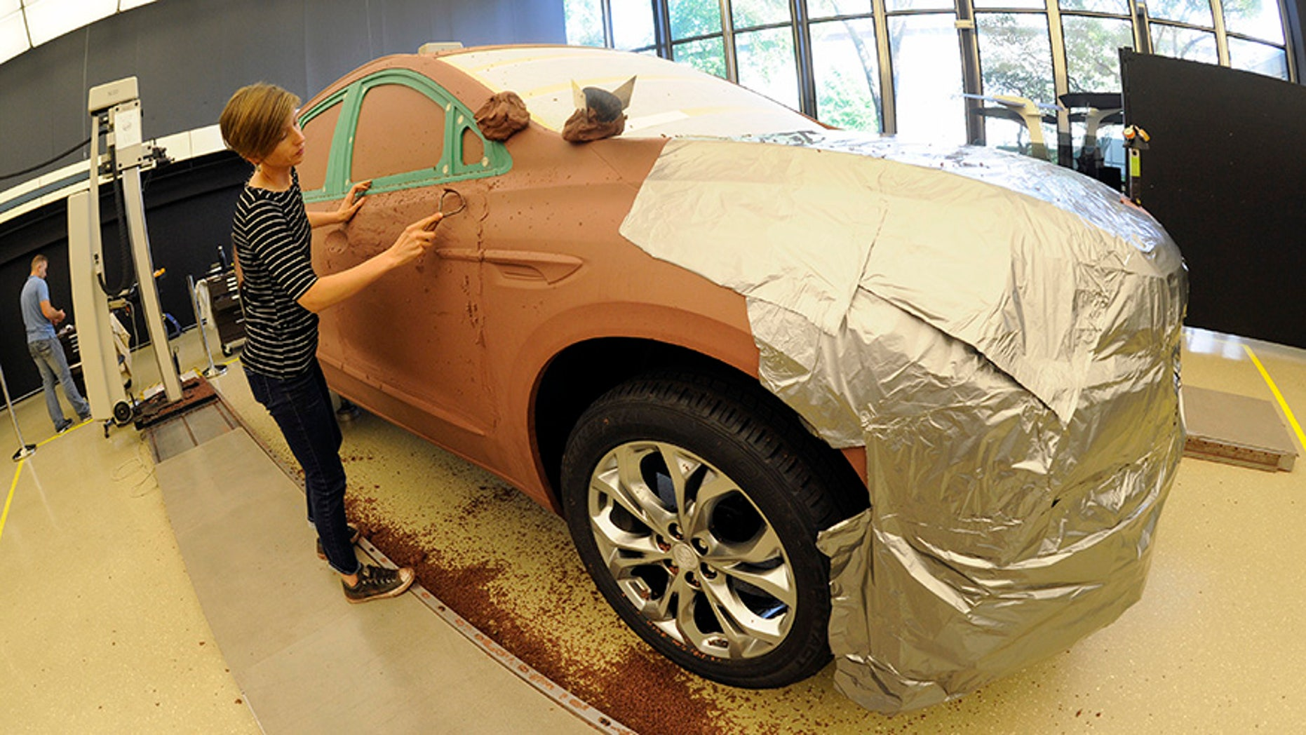 General Motors creative clay sculptor Gianna Ball smooths loose clay on a model of a 2018 Buick Enclave frame, Friday, Aug. 25, 2017 at the GM Tech Center in Warren, Mich. (AP Photo/Jose Juarez)