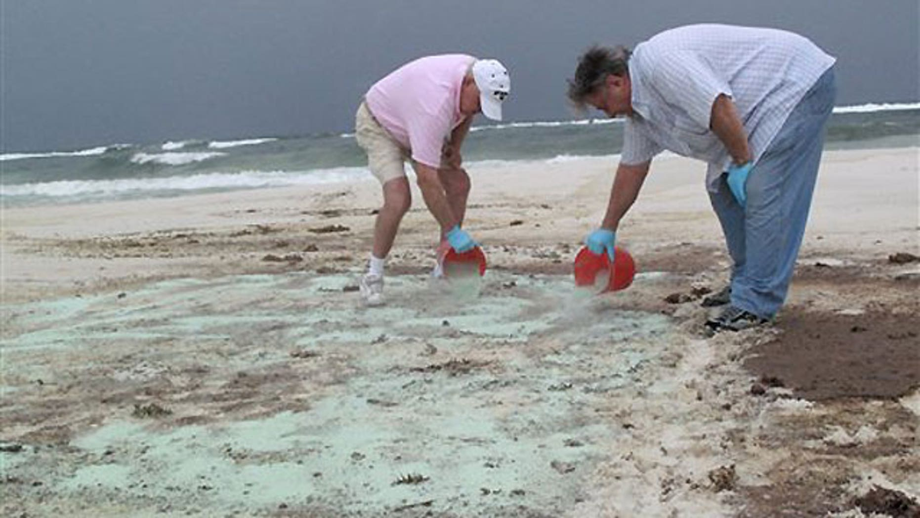 July 1: Workers demonstrate a sand-cleaning technology, called Green Tech, for evaluators from Florida's Department of Environmental Protection and BP on Pensacola Beach.