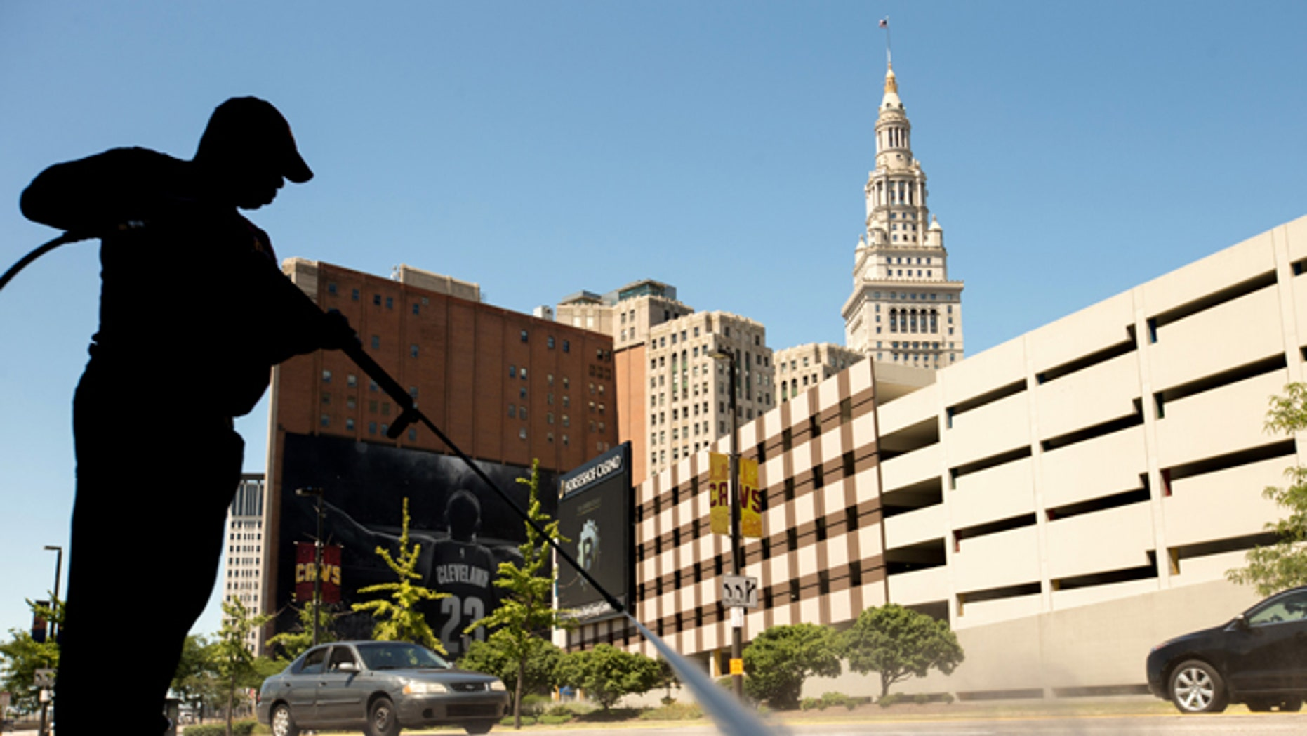 A worker cleans the sidewalk in front of the Quicken Loans Arena in Cleveland, Wednesday, Aug. 5, 2015, before Thursday's first Republican presidential debate being held at the arena. (AP Photo/Andrew Harnik)