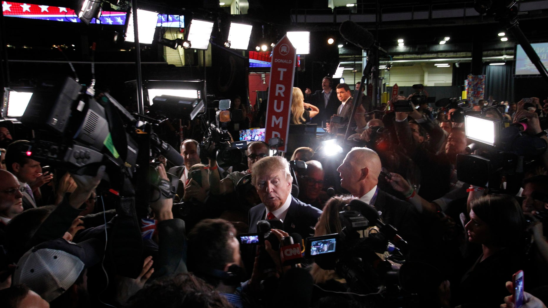 """Republican 2016 U.S. presidential candidate businessman Donald Trump is surrounded by news media in the """"spin room"""" after the conclusion of the first official Republican presidential candidates debate of the 2016 U.S. presidential campaign in Cleveland, Ohio, August 6, 2015."""