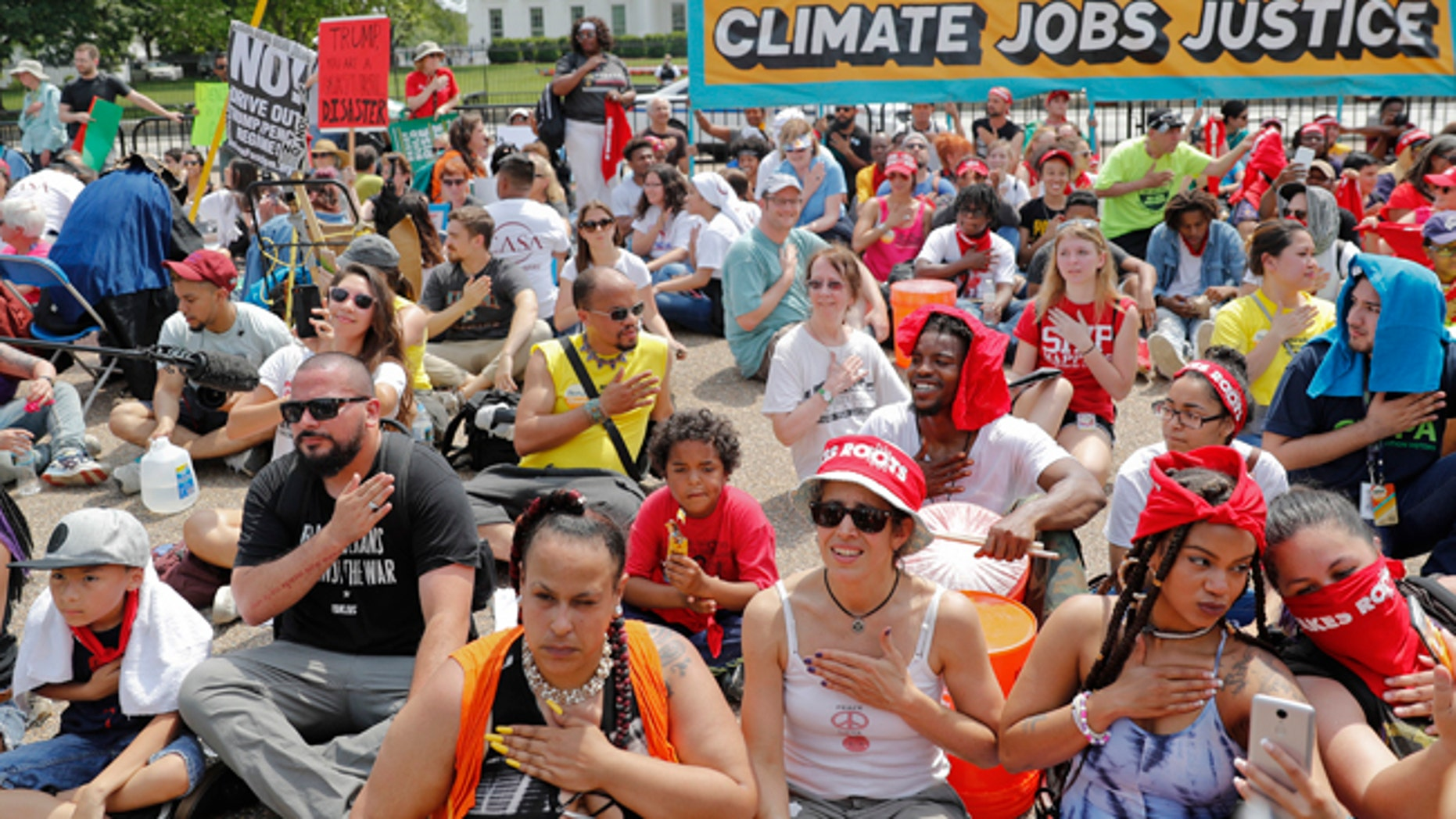Demonstrators sit on the ground along Pennsylvania Ave. in front of the White House in Washington, Saturday, April 29, 2017, during a demonstration and march. Thousands of people gathered across the country to march in protest of President Donald Trump's environmental policies, which have included rolling back restrictions on mining, oil drilling and greenhouse gas emissions at coal-fired power plants.