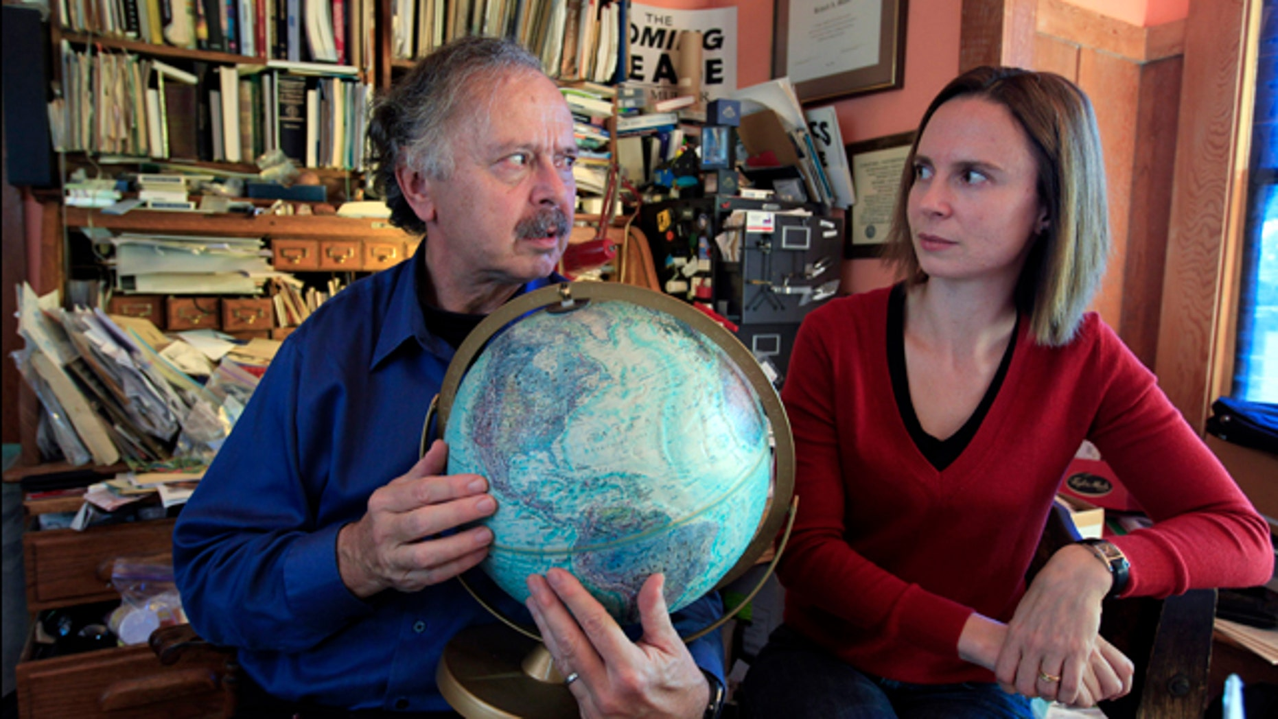 Richard Muller, left, and his daughter, Elizabeth Muller, hold a globe as they talk about their study on climate at their home in Berkeley, Calif.