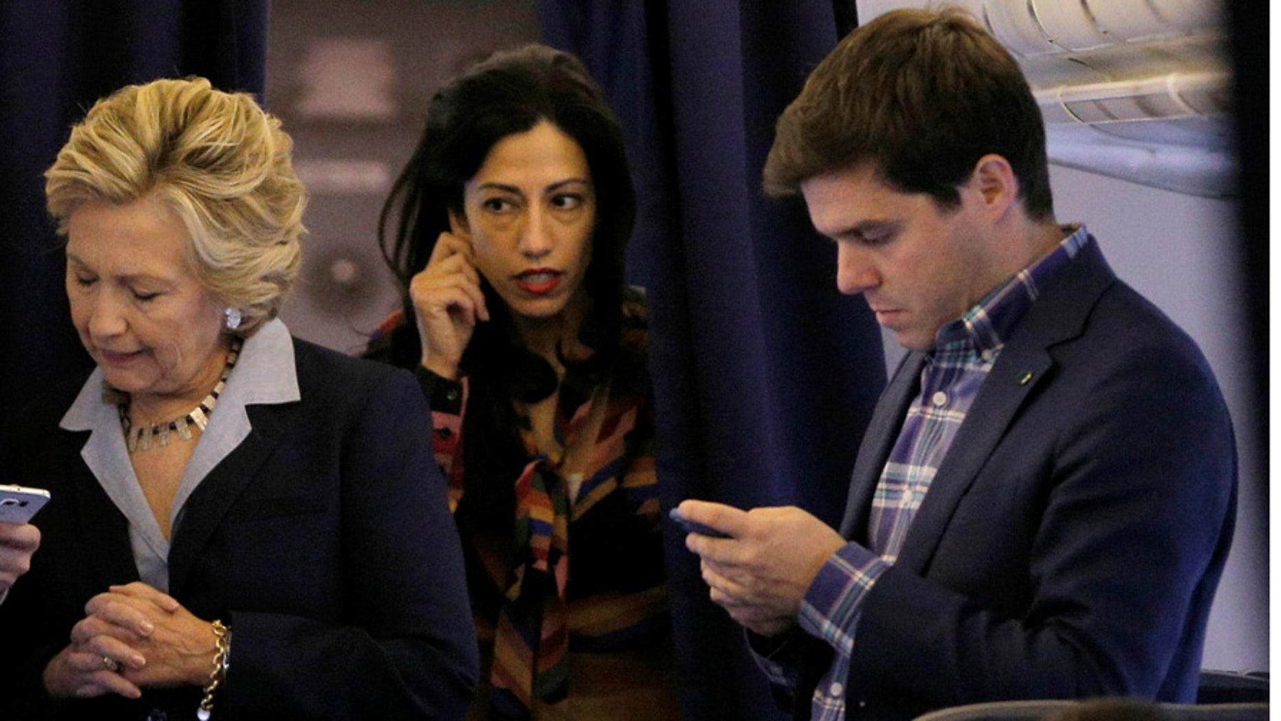Hillary Clinton stands with longtime aide Huma Abedin, middle, and press secretary Nick Merrill, right, onboard her campaign plane in October 2016.
