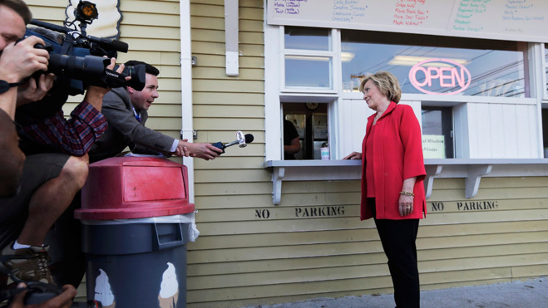 July 3, 2015: Democratic presidential candidate Hillary Rodham Clinton listens to a reporter's question as she waits for her ice cream at Dairy Twirl in New Hampshire.