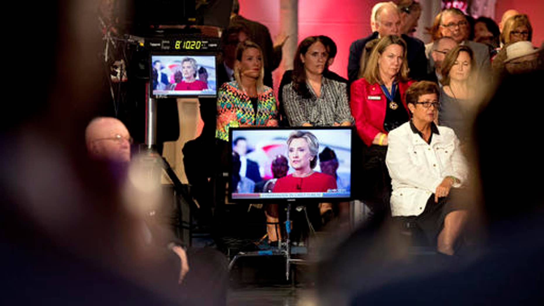 Members of the audience listen to Democratic presidential candidate Hillary Clinton, displayed on television screens as she speaks with 'Today' show co-anchor Matt Lauer at the NBC Commander-In-Chief Forum held at the Intrepid Sea, Air and Space museum aboard the decommissioned aircraft carrier Intrepid, New York, Wednesday, Sept. 7, 2016.