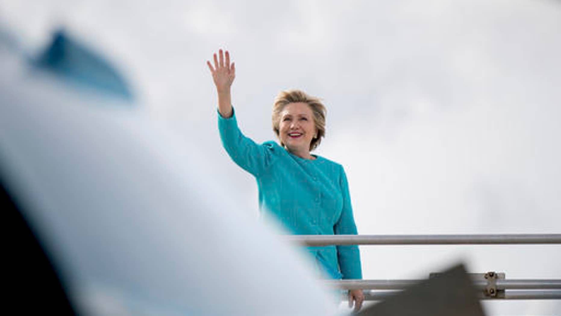 Democratic presidential candidate Hillary Clinton waves before boarding her campaign plane at Miami International Airport in Miami, Wednesday, Oct. 26, 2016, to travel to Lake Worth, Fla. for a rally.