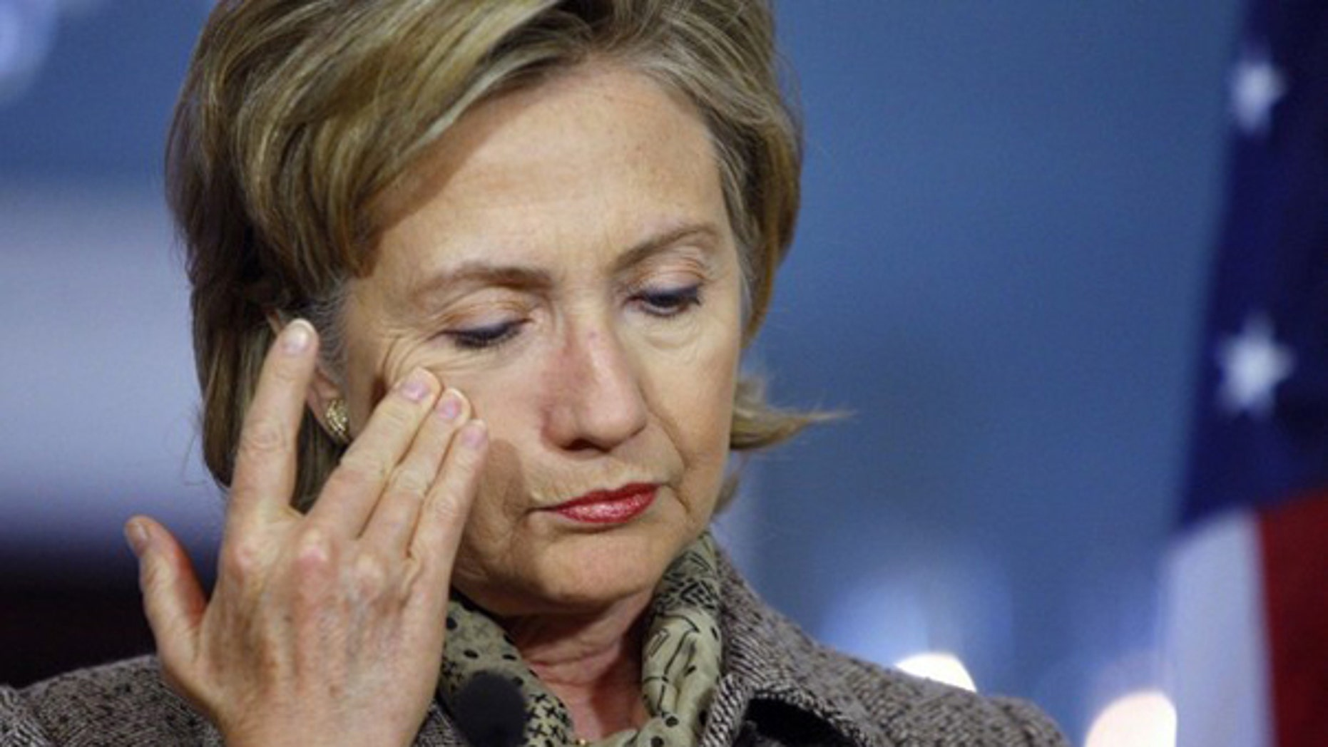 Hillary Clinton wipes her face during a press conference in Washington.