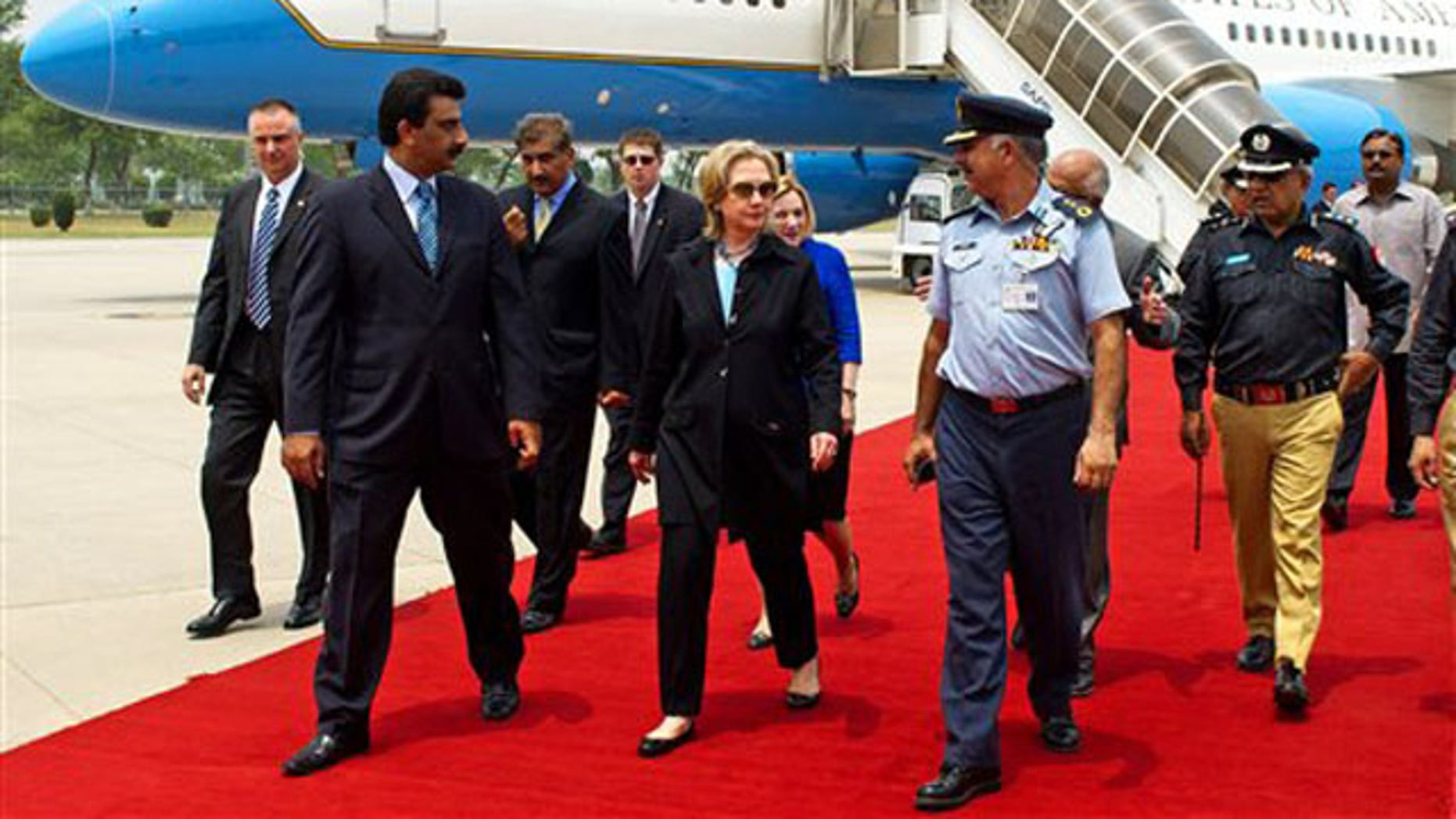 Secretary of State Hillary Clinton, center, walks on the red carpet upon her arrival at PAF Base Chakala in Islamabad July 18. (AP Photo)
