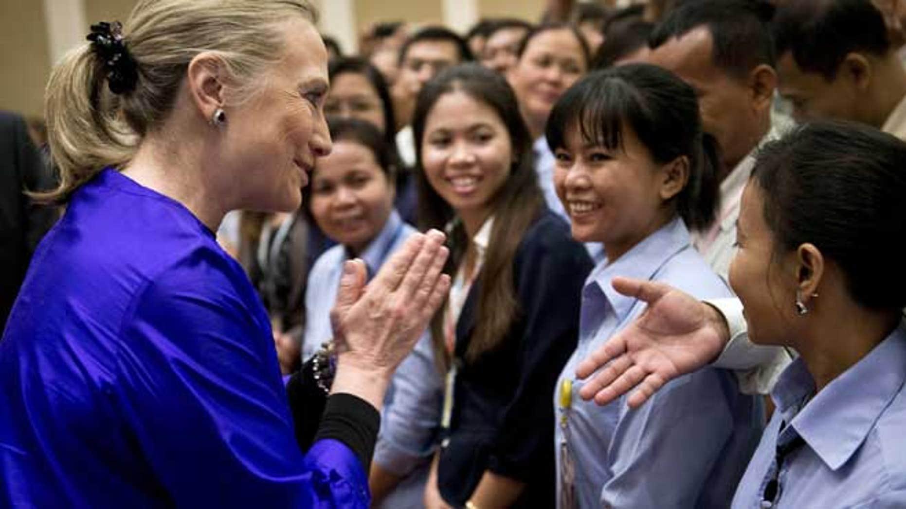 July 13, 2012: U.S. Secretary of State Hillary Rodham Clinton, left, greets U.S. Embassy staff at the Le Royal hotel in Phnom Penh, Cambodia.