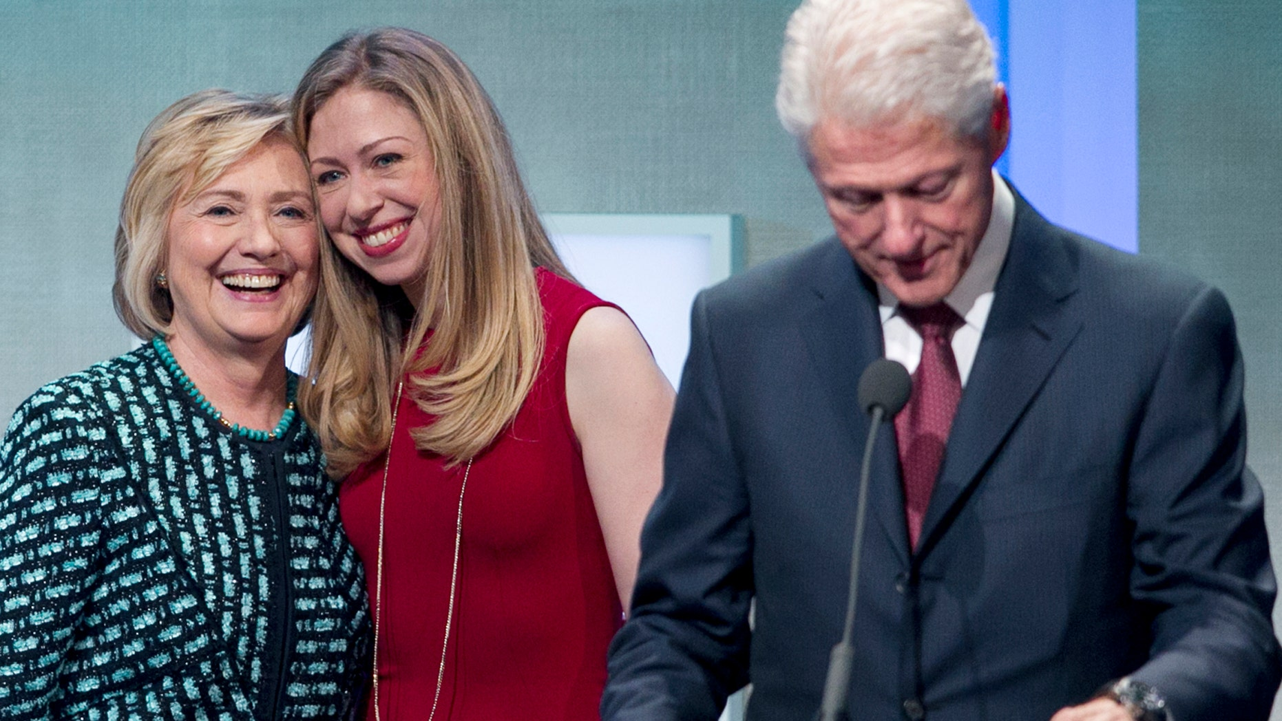 Former President Bill Clinton prepares to make remarks at the Clinton Global Initiative while his wife, Hillary Rodham Clinton, and daughter, Chelsea, take the stage with him, Tuesday, Sept. 24, 2013 in New York.