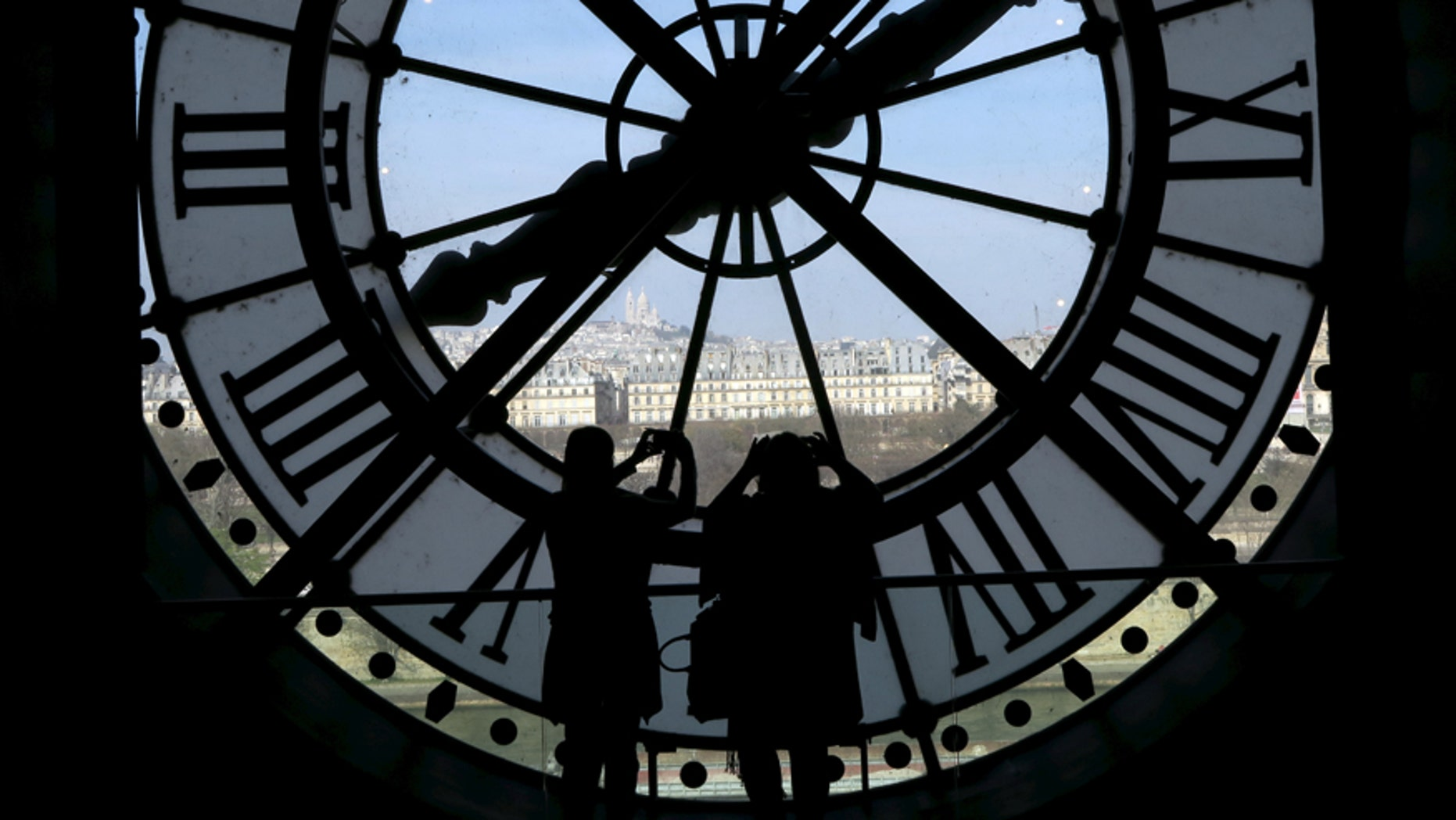 File photo - Visitors at the Musee d'Orsay are seen in silhouette as they take pictures from behind a giant clock face at the former Orsay railway station, with a view of the Sacre Coeur Basilica (rear), in Paris April 8, 2015. (REUTERS/John Schults)