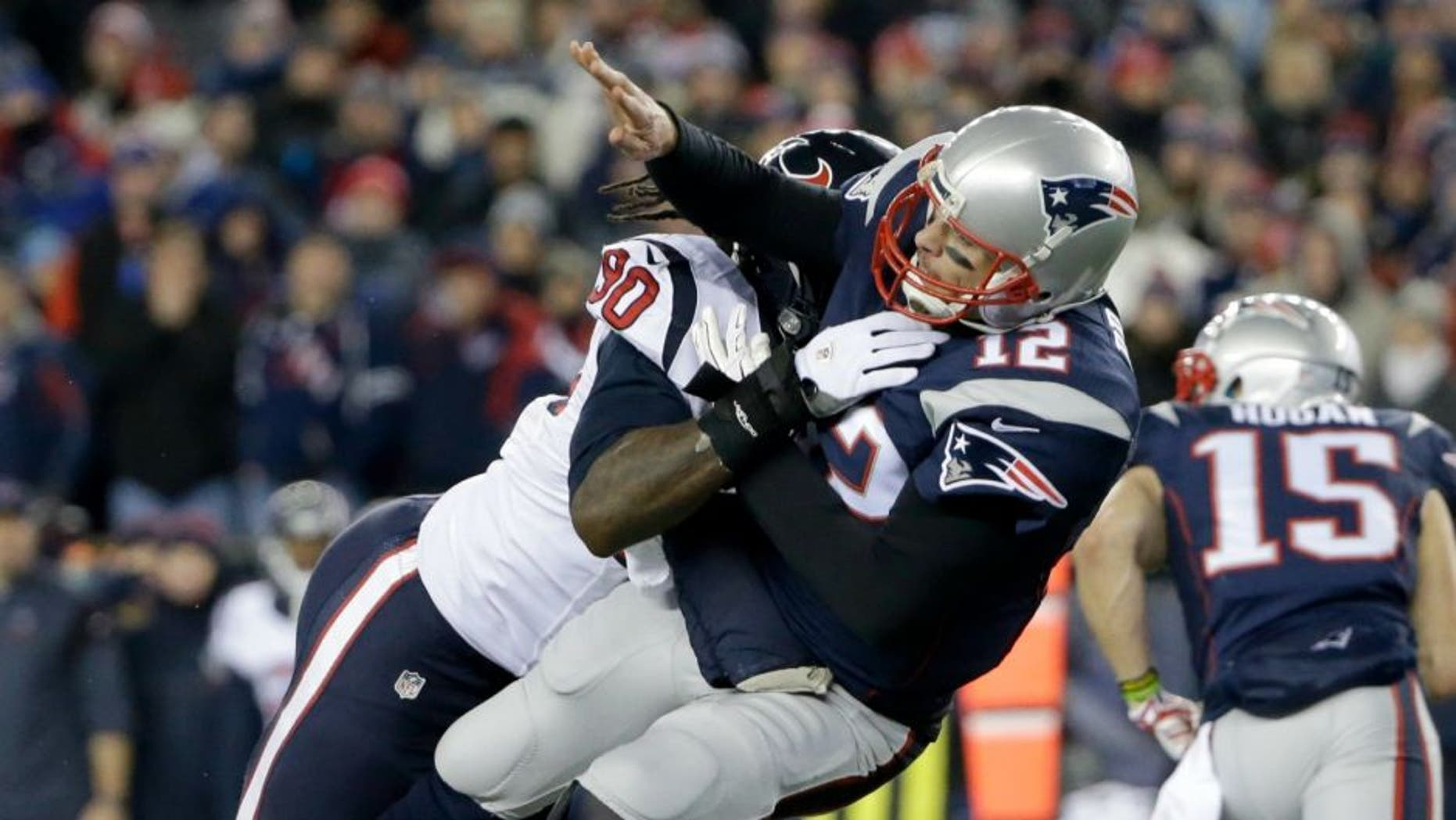 Houston Texans defensive end Jadeveon Clowney (90) levels New England Patriots quarterback Tom Brady (12) after he threw a pass during the first half of an NFL divisional playoff football game, Saturday, Jan. 14, 2017, in Foxborough, Mass. (AP Photo/Elise Amendola)