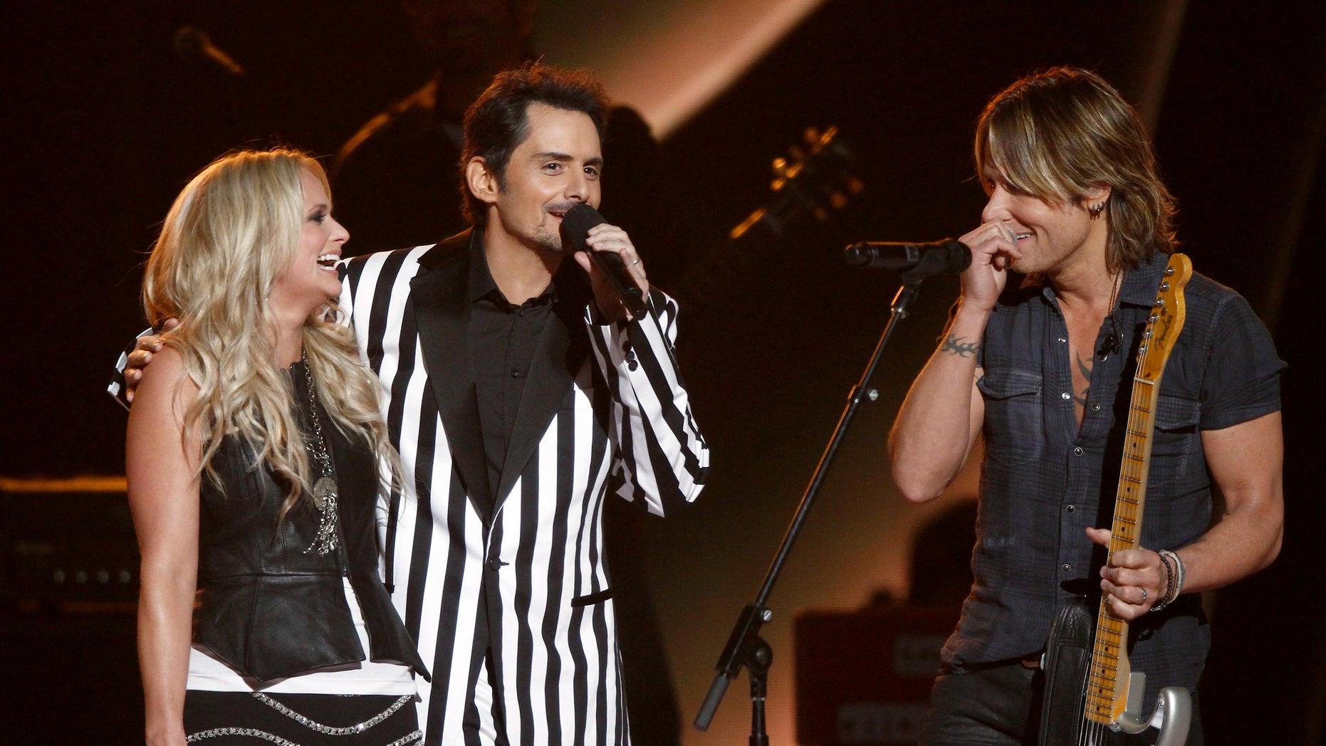 Miranda Lambert, left, Brad Paisley, center, and Keith Urban appear onstage at the 47th annual CMA Awards at Bridgestone Arena on Wednesday, Nov. 6, 2013, in Nashville, Tenn. (Photo by Wade Payne/Invision/AP)
