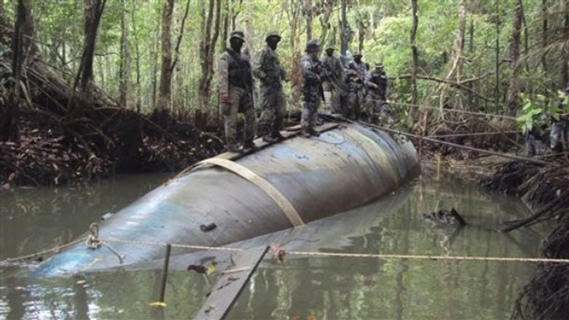 Soldiers stand on a seized submarine in the jungle region of La Loma in Ecuador, Saturday July 3, 2010. DEA officials said that the diesel electric-powered submarine was constructed in a remote jungle and captured near a tributary close to the Ecuador-Colombia border and is capable of transporting tons of cocaine.