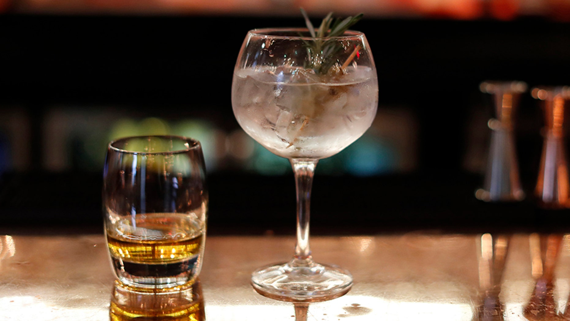 A Gin Cocktail and glass of whisky sit side by side on a bar.