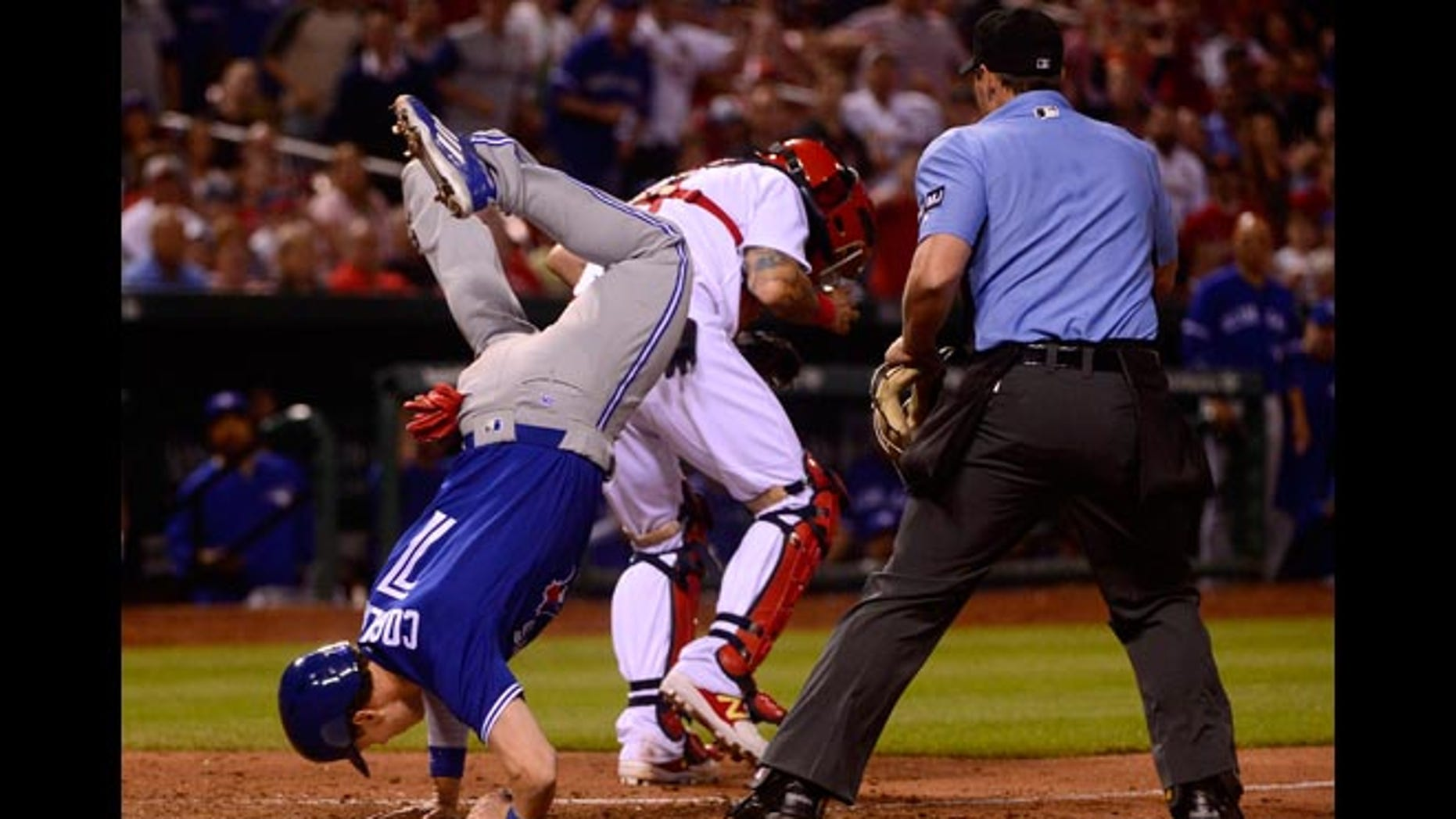Chris Coghlan touches home plate after leaping over Yadier Molina.