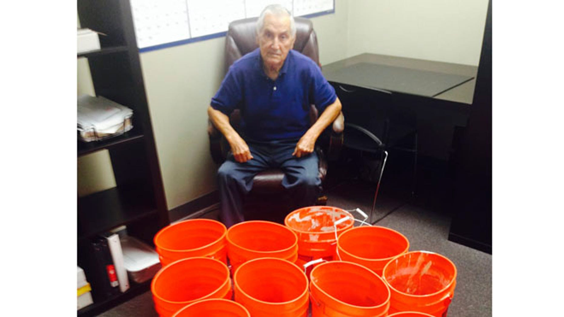 July 31, 2014: This image provided by Andres Carrasco shows him in his office in Los Angeles with buckets of change he won as a partial settlement in a 2012 lawsuit against Adrianas Insurance Services, a Rancho Cucamonga, Calif.-based company.
