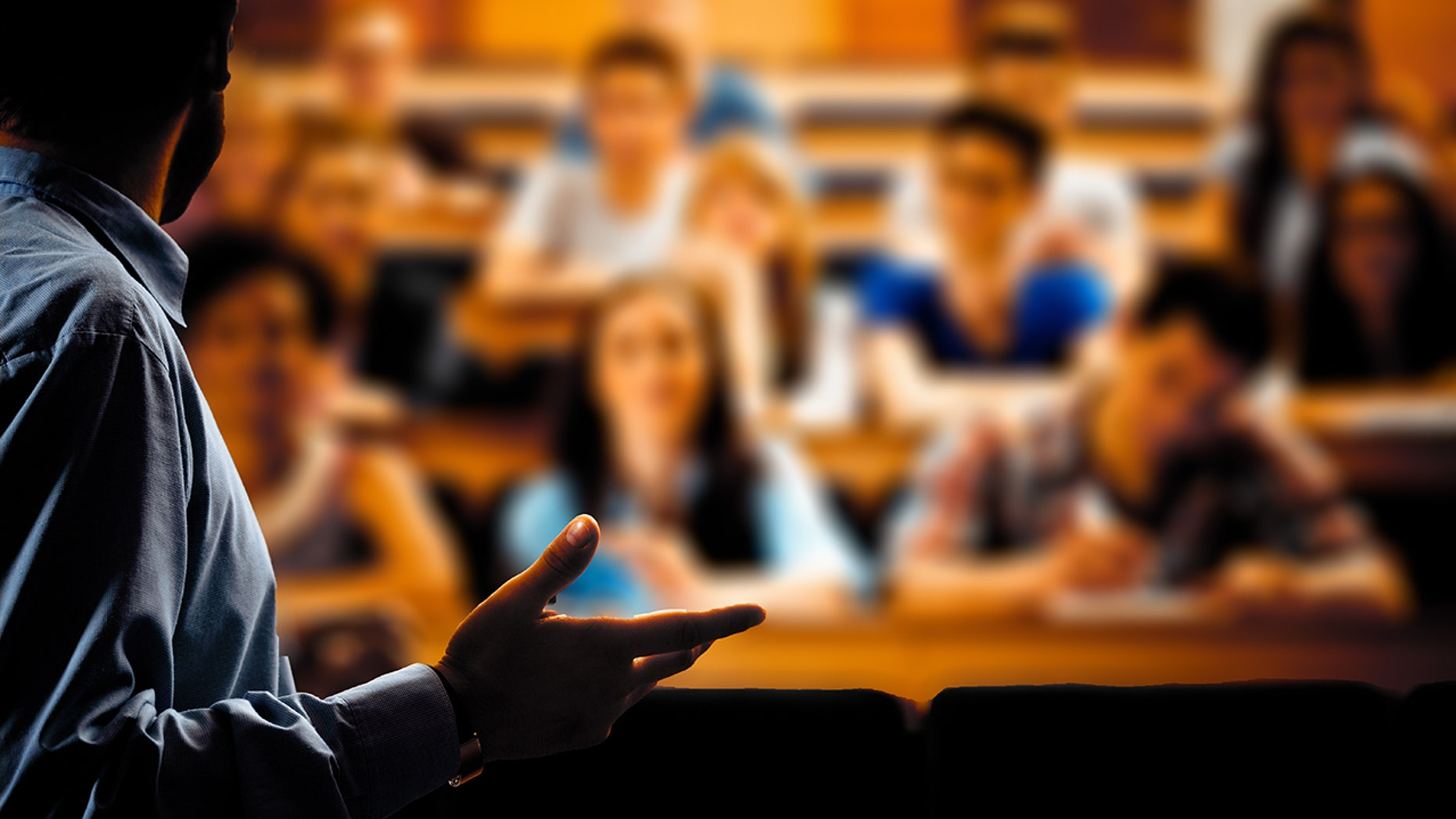 Large group of students sitting in the lecture hall at university and listening to their teacher. Focus on the professor. Dark tones.
