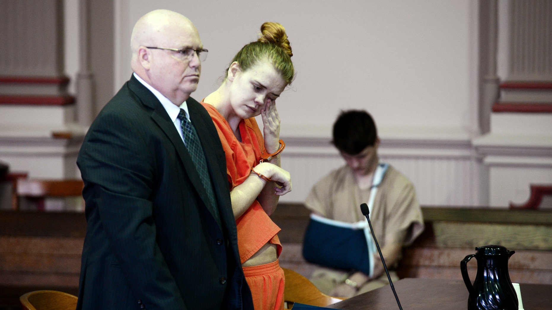 Emile Weaver, center, wipes her eyes while standing next to her attorney.