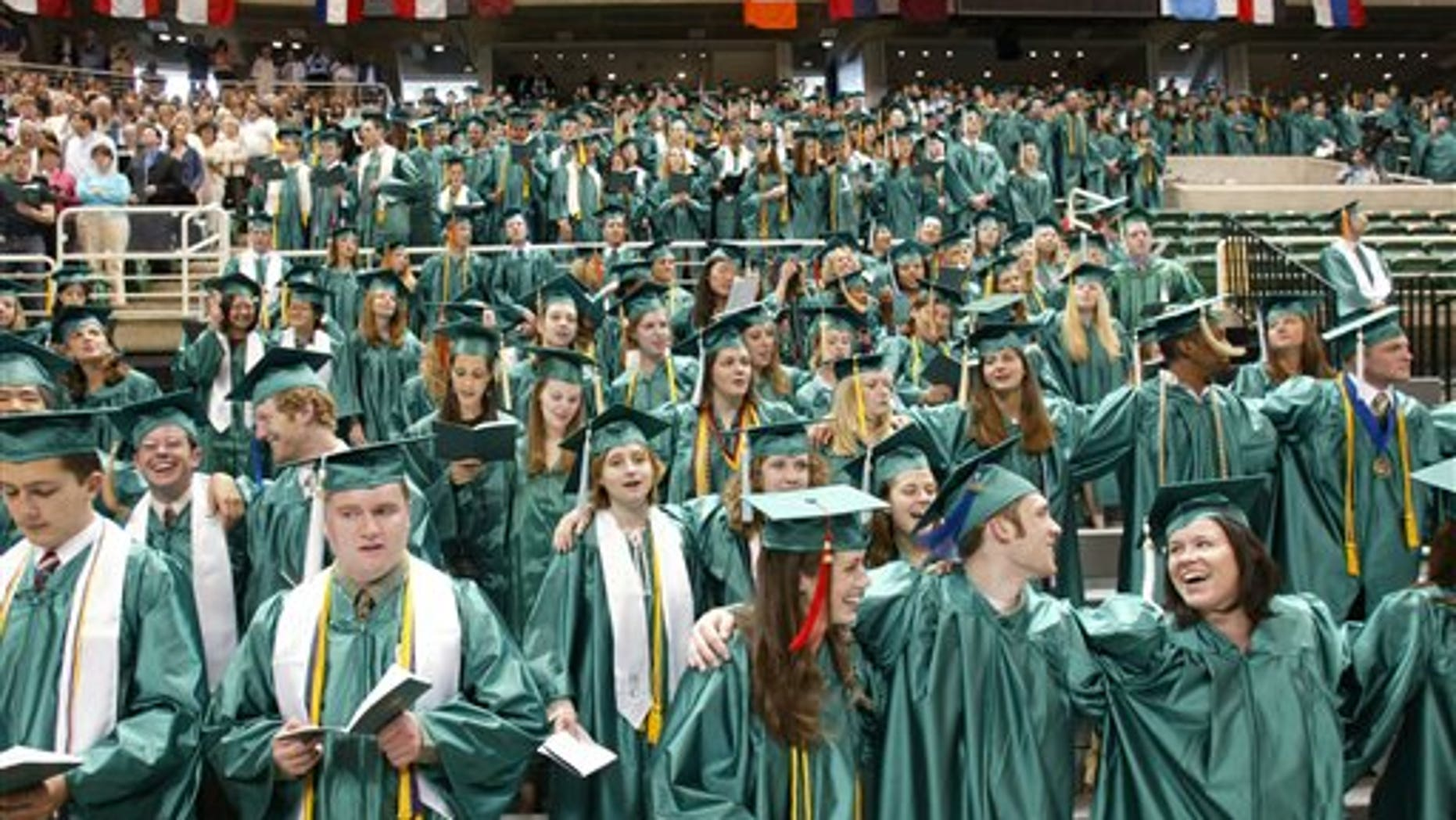 Michigan State University graduates as they sing their school's Alma Mater at the close of convocation ceremonies in East Lansing, Mich.