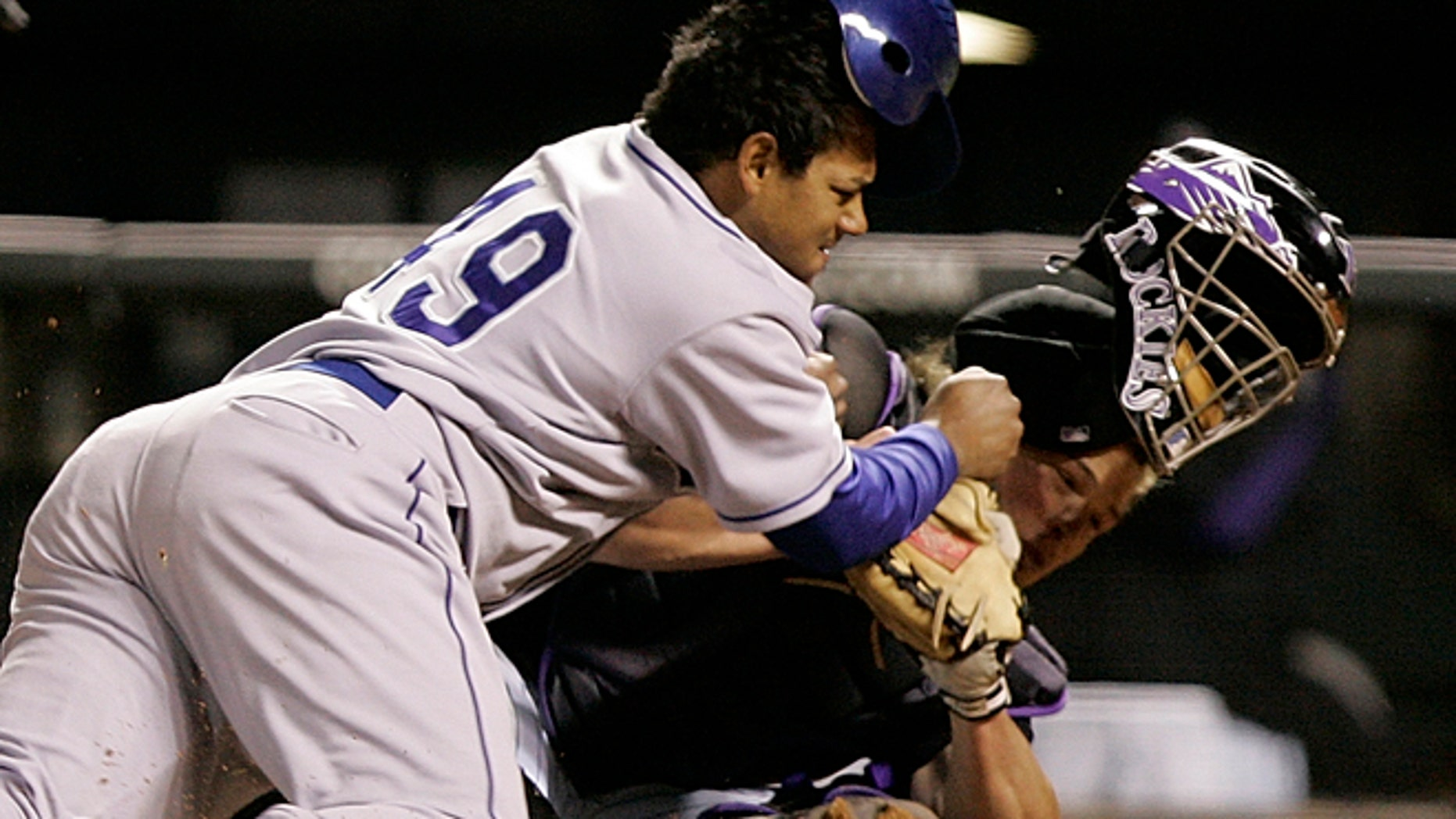 FILE 2006: Los Angeles Dodgers' Delwyn Young, left, is out at home plate as he collides with Colorado Rockies catcher JD Closser during the seventh inning of a baseball game in Denver.