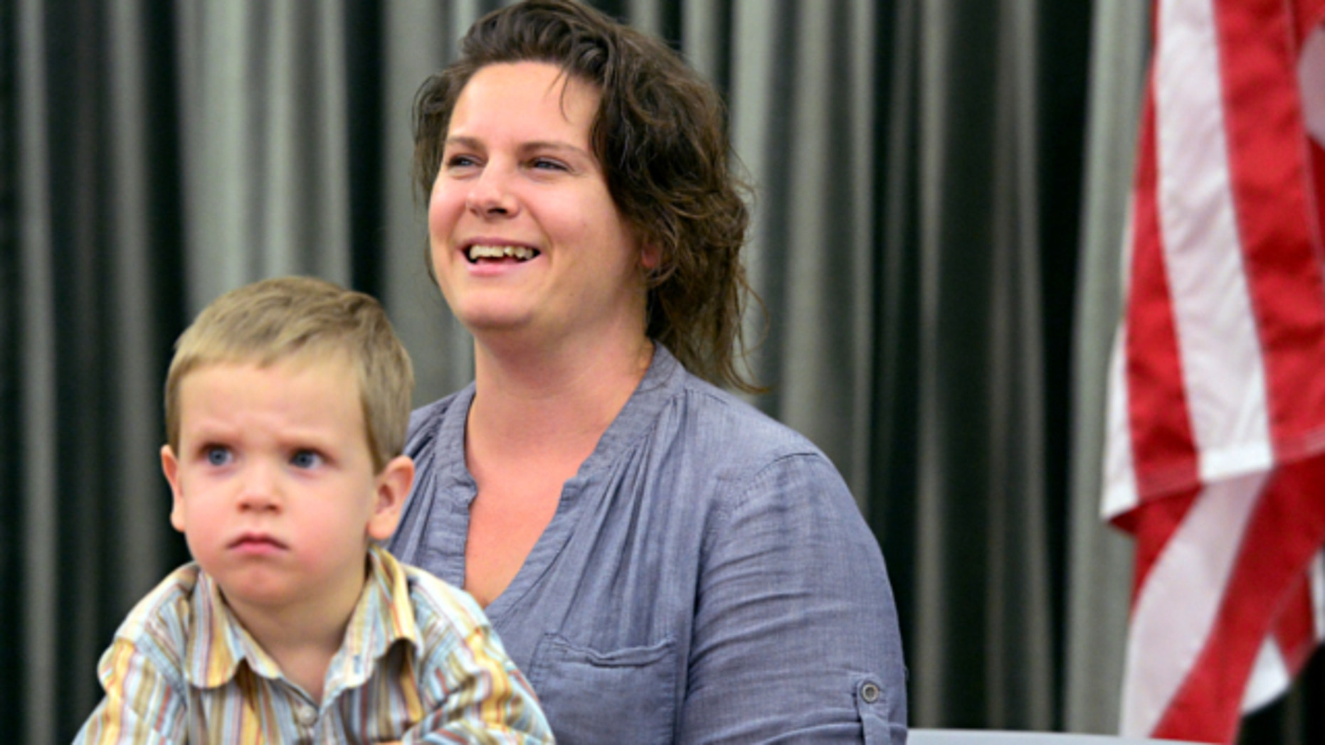 May 28, 2013: Brandy Turner, right, with her three-year-old son, Luke Turner, speaks to media during a news conference at the Denver International Airport.