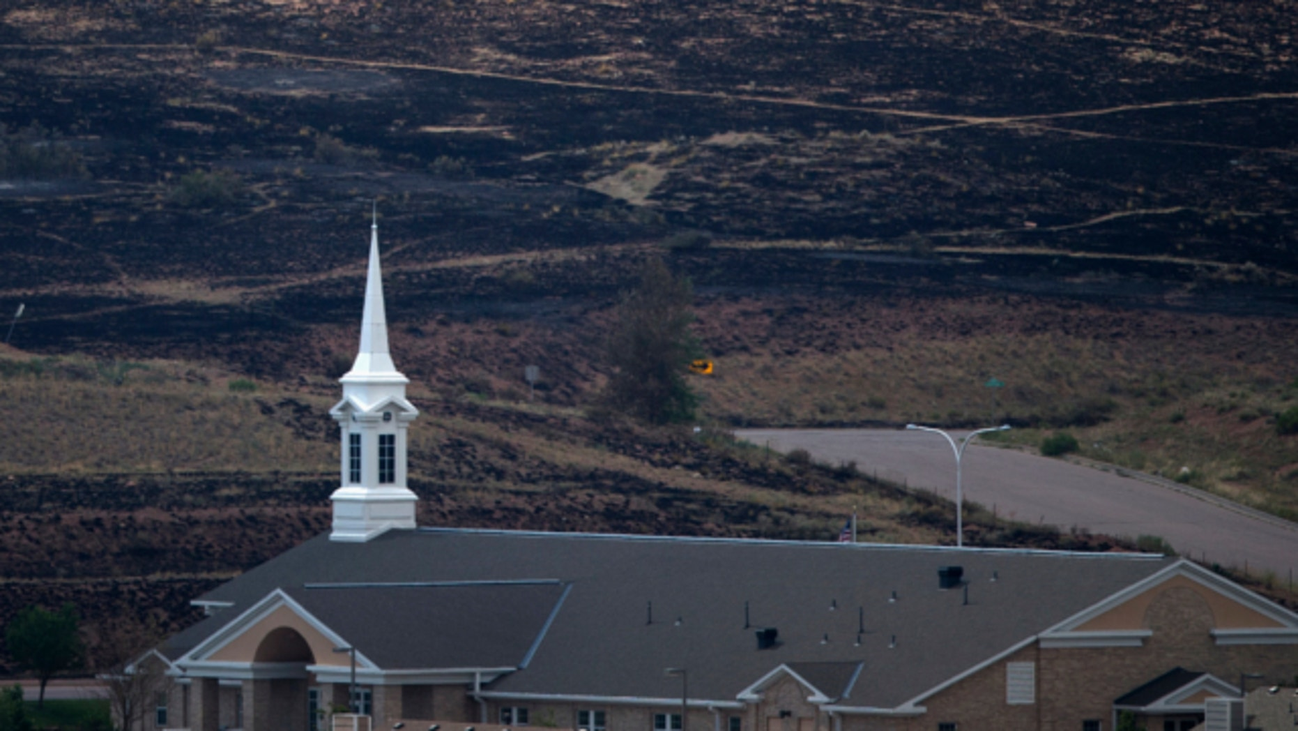 FILE: June 30, 2012. A church, which survived the Waldo Canyon Fire, is backdropped by a charred hillside in Colorado Springs, Colorado.