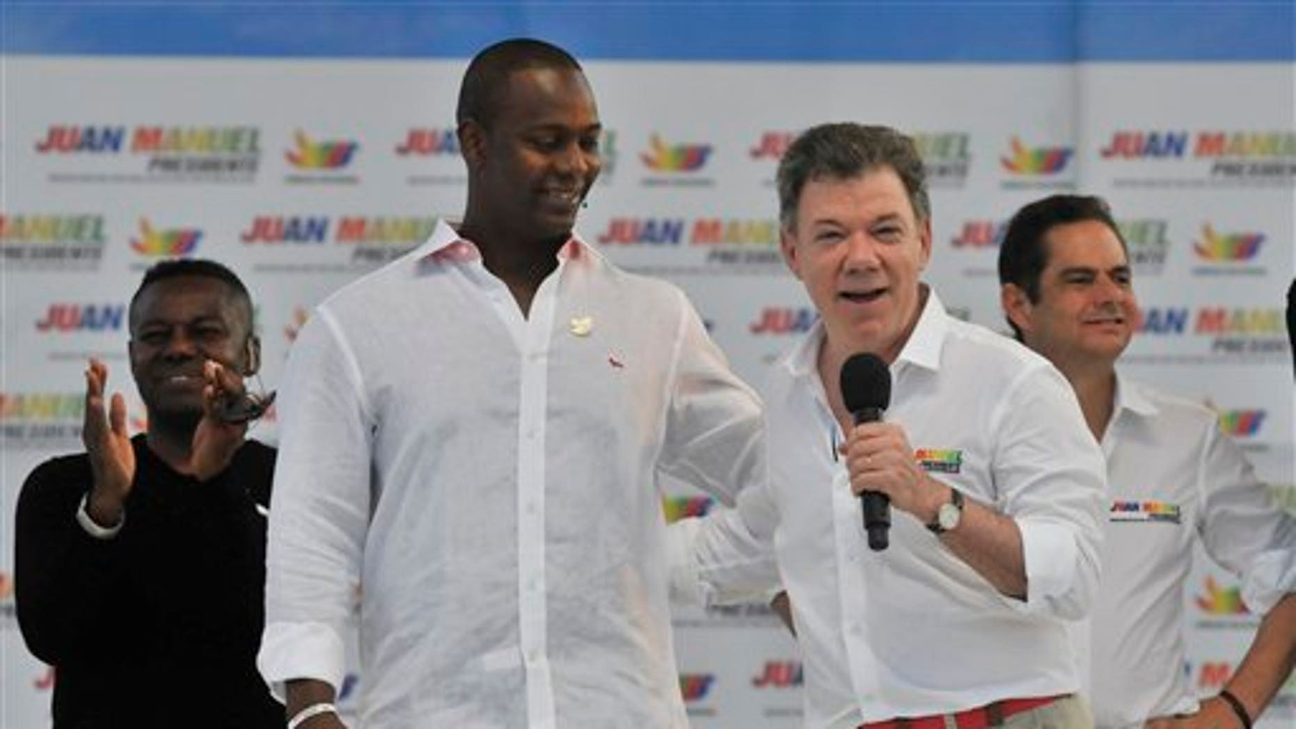 Colombia's President Juan Manuel Santos speaks next to retired baseball player Edgar Renteria during a campaign rally at the Tomas Arrieta baseball stadium in Barranquilla, Colombia, Sunday, March 16, 2014. Santos, who is running for re-election, said on a televised statement on Tuesday, March 18, that he suffered an accident of incontinence product of surgery he underwent a year and a half ago to remove prostate cancer, that according to his doctor the accident is normal in patients who have suffered such intervention and that his health is optimal. (AP Photo)