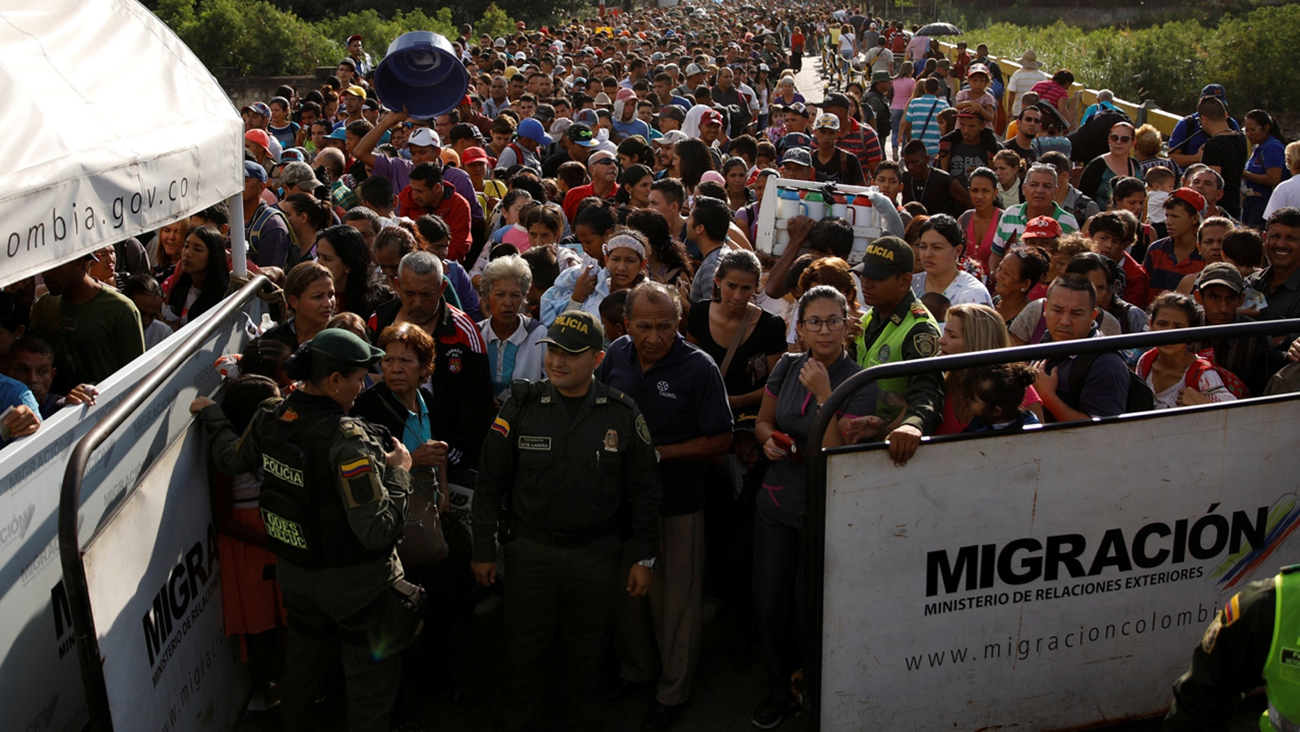 Colombian police officers stand in front of people assembling to try to cross into Colombia from Venezuela last month via Simón Bolívar International Bridge in Cúcuta, Colombia.