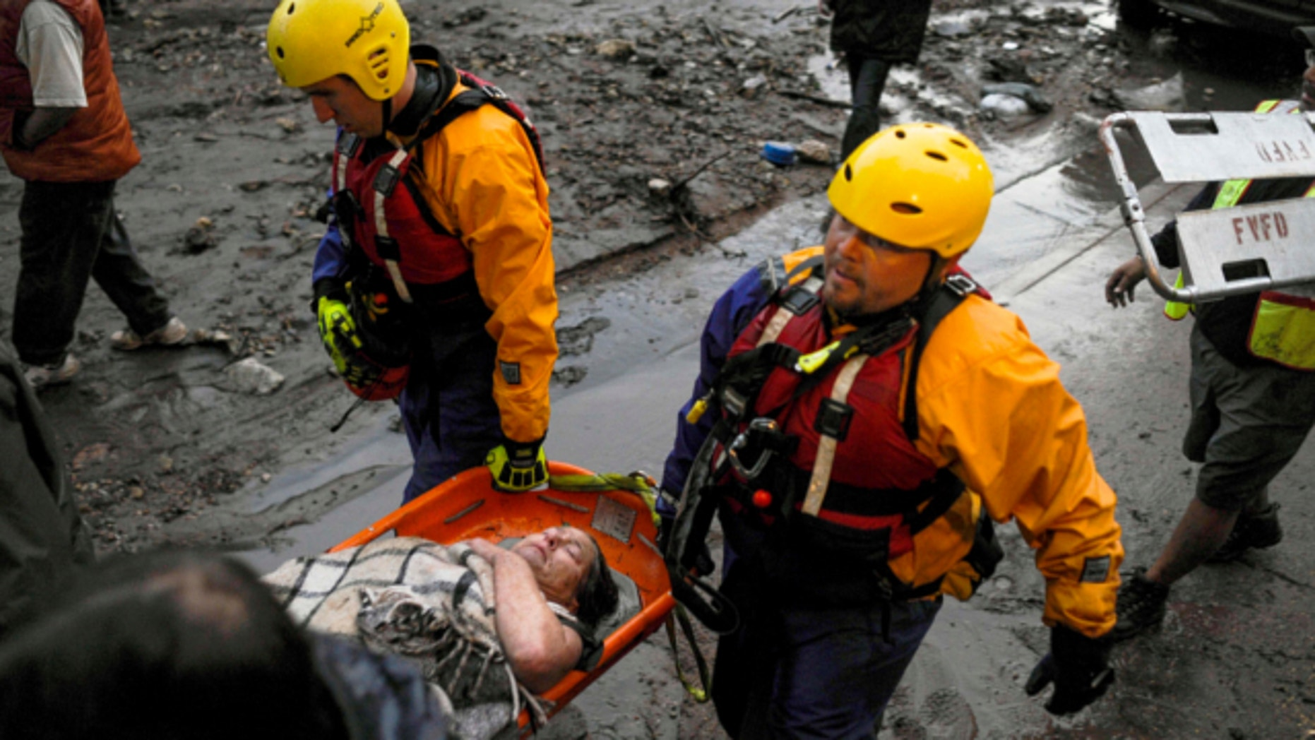 Aug. 9, 2013: The Fountain Water Rescue team assists a woman down Canon Avenues after she broke her leg climbing to safety to avoid the flash flood that ripped through downtown in Manitou, Colo.
