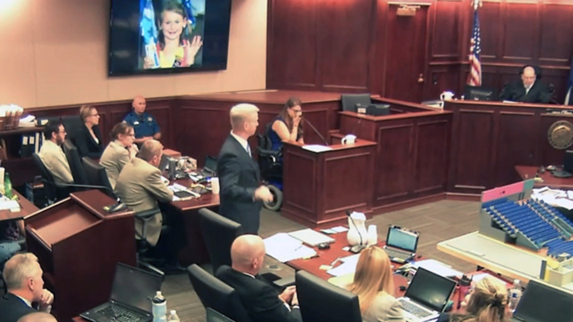 June 19, 2015: In this image taken from video, Ashley Moser, center top, who lost her 6-year-old daughter Veronica in the 2012 Colorado movie theater mass shooting, cries while testifying as a picture of her slain daughter is shown, top, during the trial of theater shooter James Holmes, pictured at top left, in Centennial, Colo. (AP)